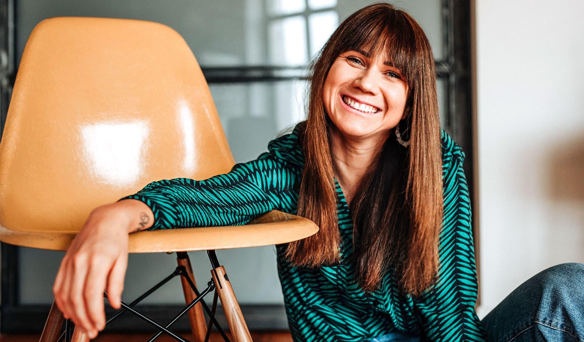 Louisa Dellert auf einen Stuhl gestützt