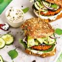 Burger mit Lupinen-Süßkartoffel-Patties und Zucchini auf einem Teller.