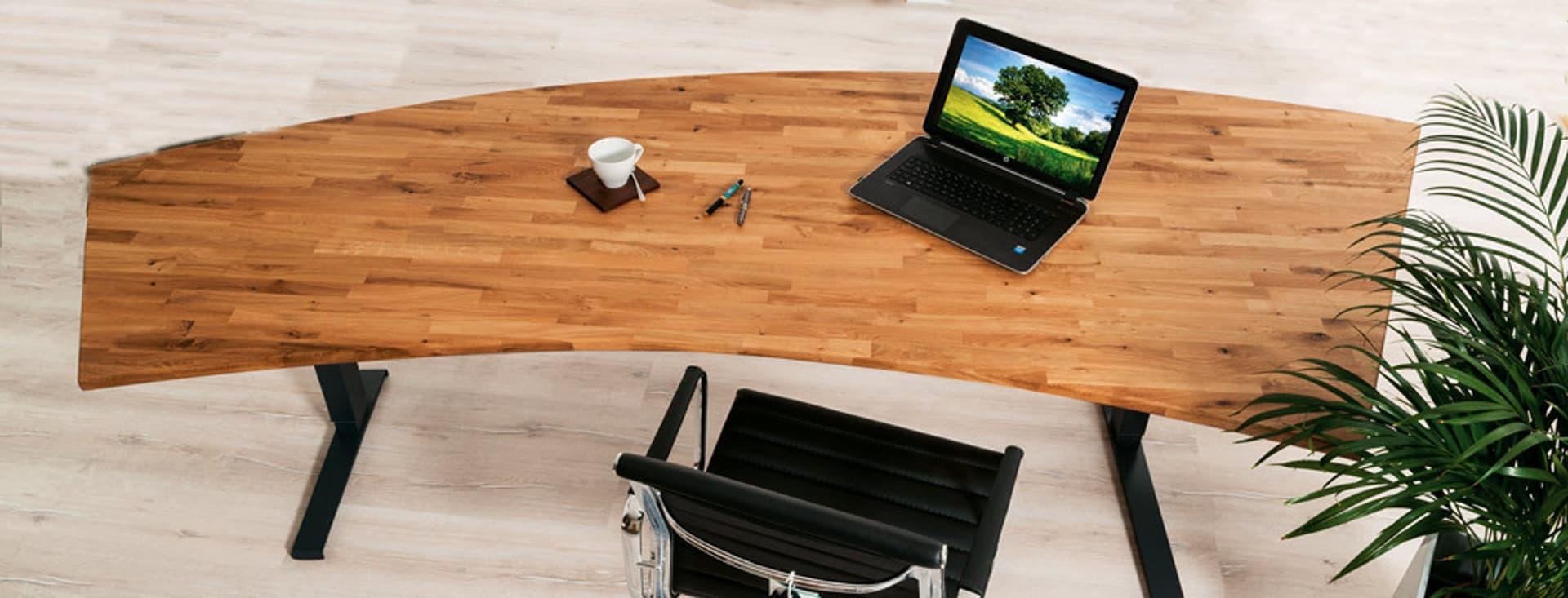 Geschwungene Arbeitsplatte aus Holz. Darauf ein Labtop und dabei steht ein Schreibtischstuhl