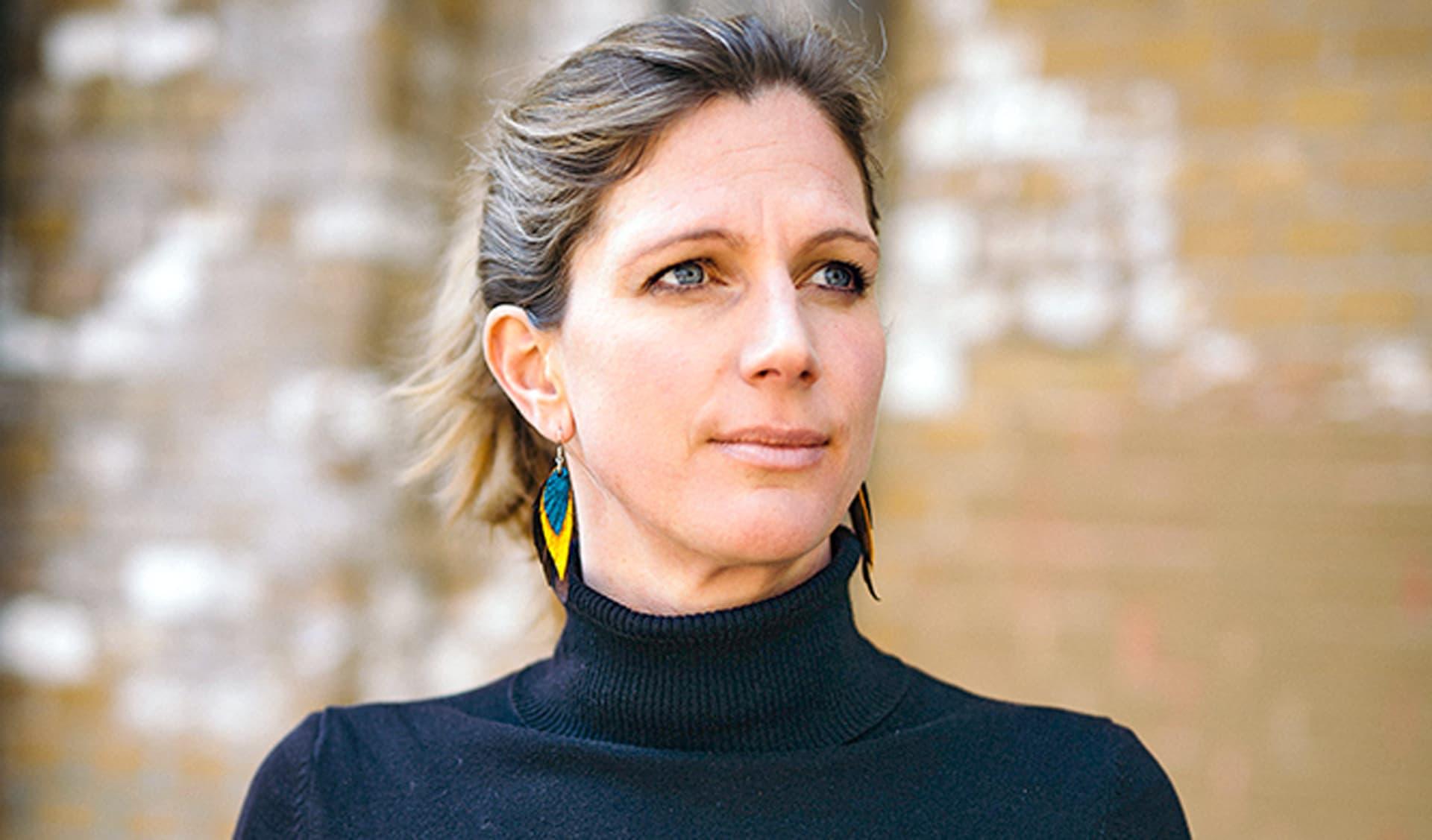 Maja Göpel im Porträt. Sie trägt einen schwarzen Rollkragenpullover und lange Ohrringe