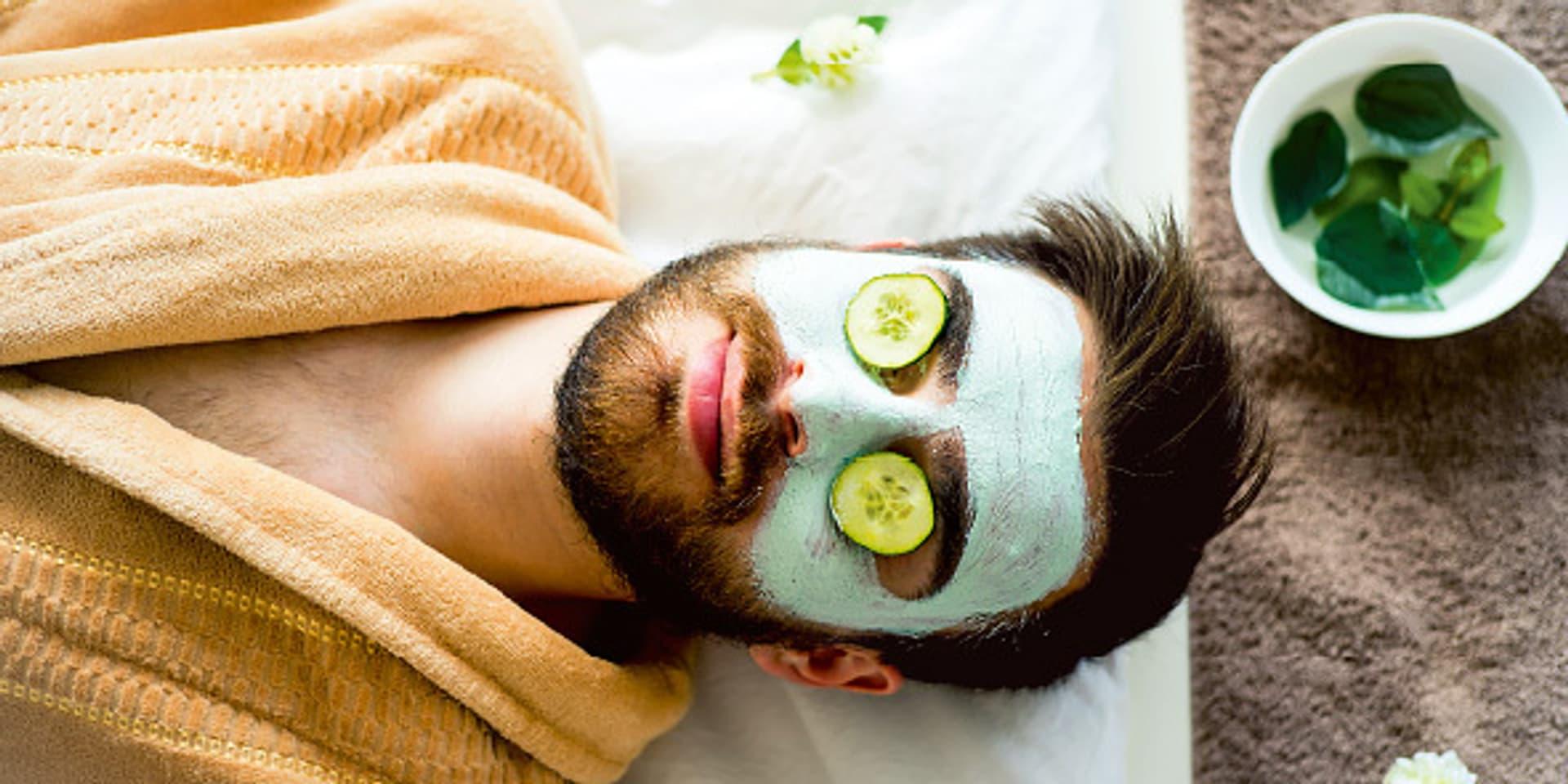 Ein Mann mit einer Crememaske im Gesicht und Gurkenscheiben auf den Augen.
