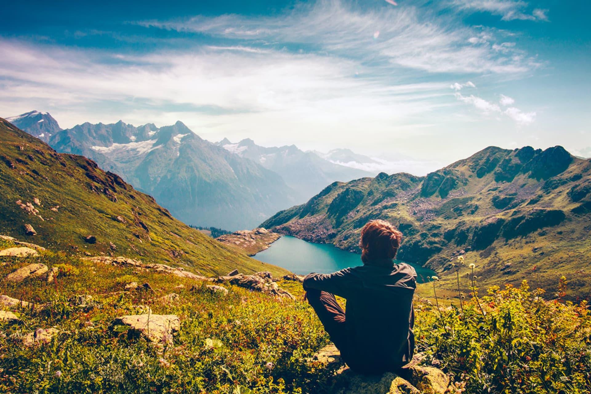 Ein Mann sitzt auf einem Berg und schaut auf einen See.