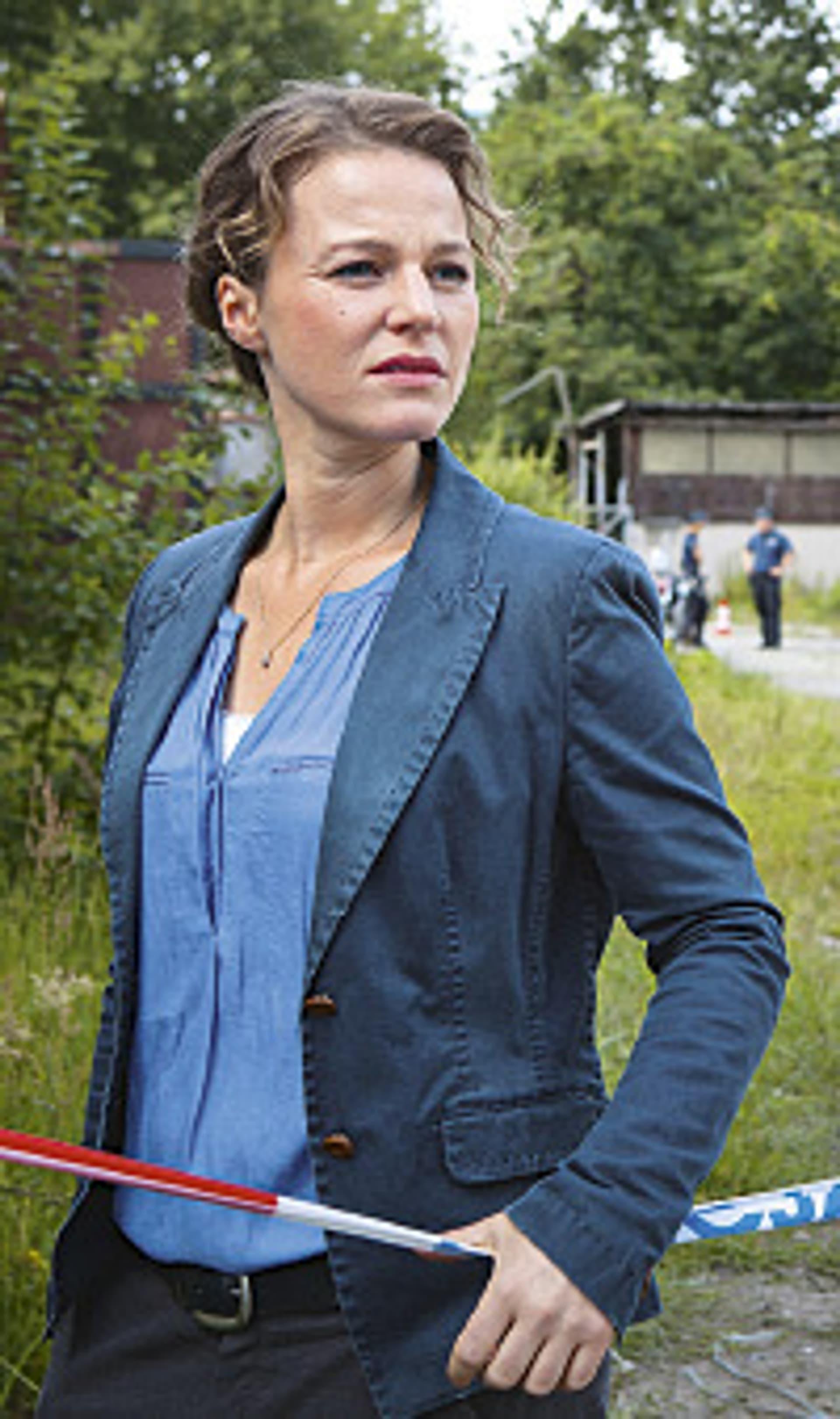 Maria Simon als Kriminalhauptkommissarin Olga Lenski im Polizeiruf 110 vor einer Absperrung stehend.