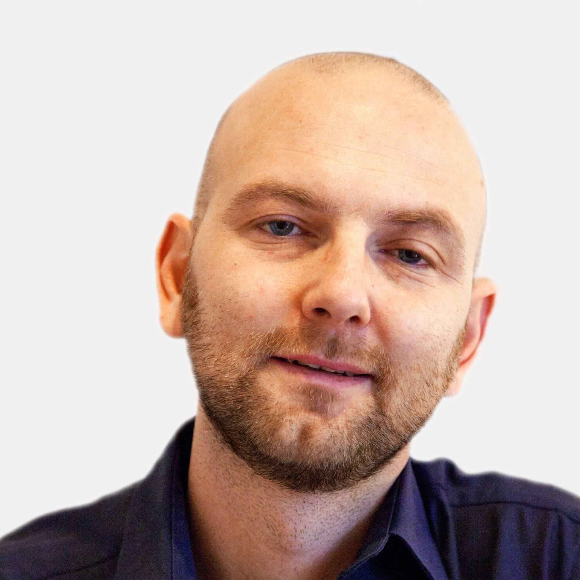 Ein Mann mit Glatze und dunkelblauem Hemd