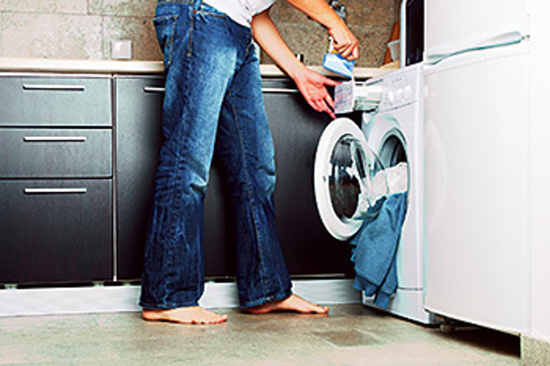 Der Ausschnitt von einem Mensch in Jeans, der Waschmittel in die Waschmaschine fällt
