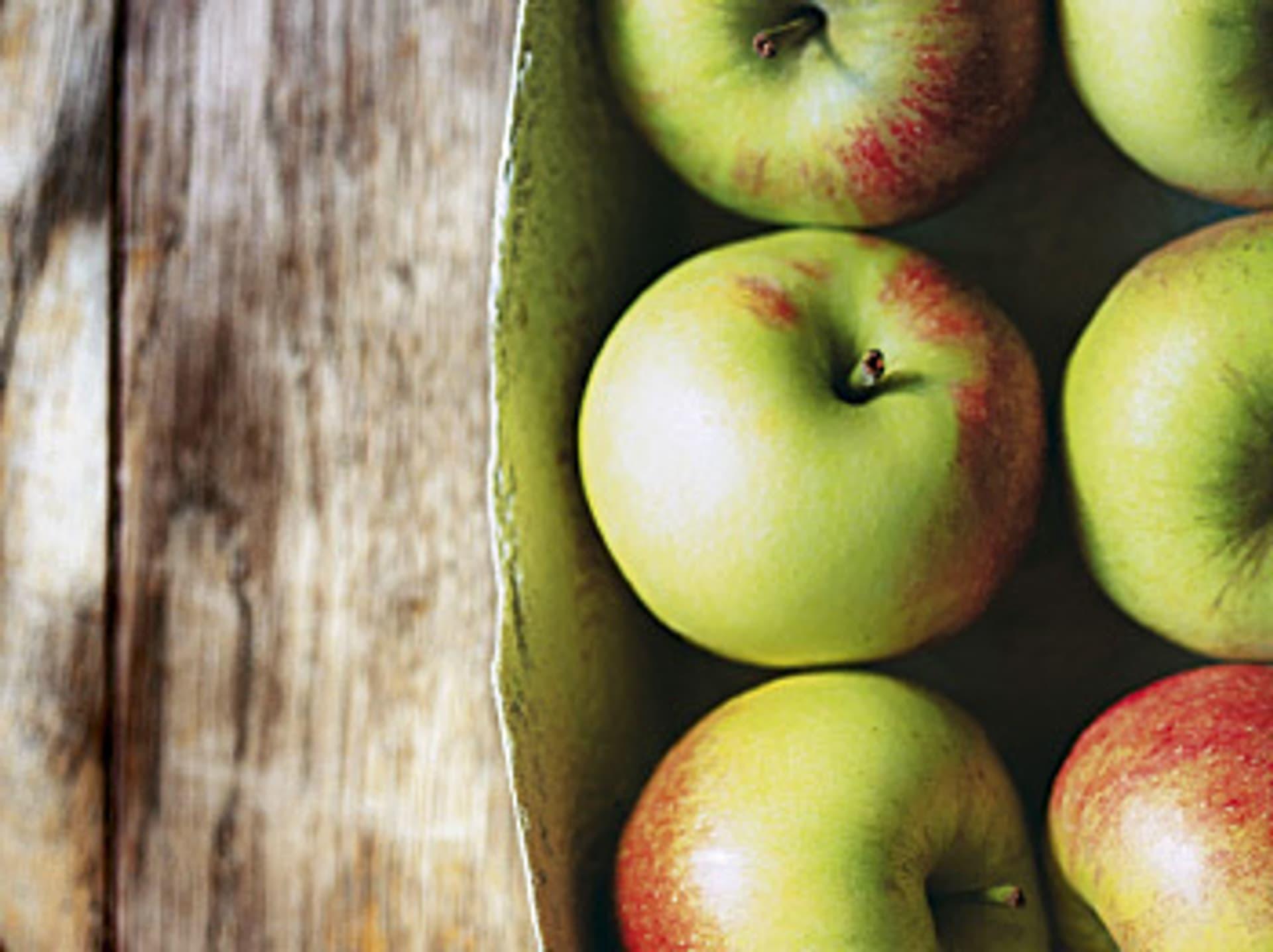 Nahaufnahme von grün-roten Äpfeln, die in einer Pappschachtel liegen.