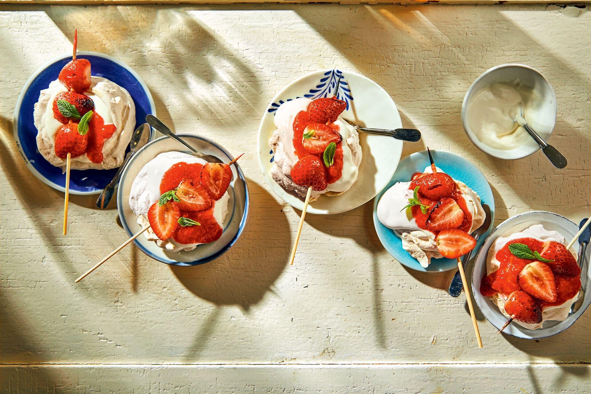 Mini-Baisers mit Grill-Erdbeeren in kleinen Schälchen.