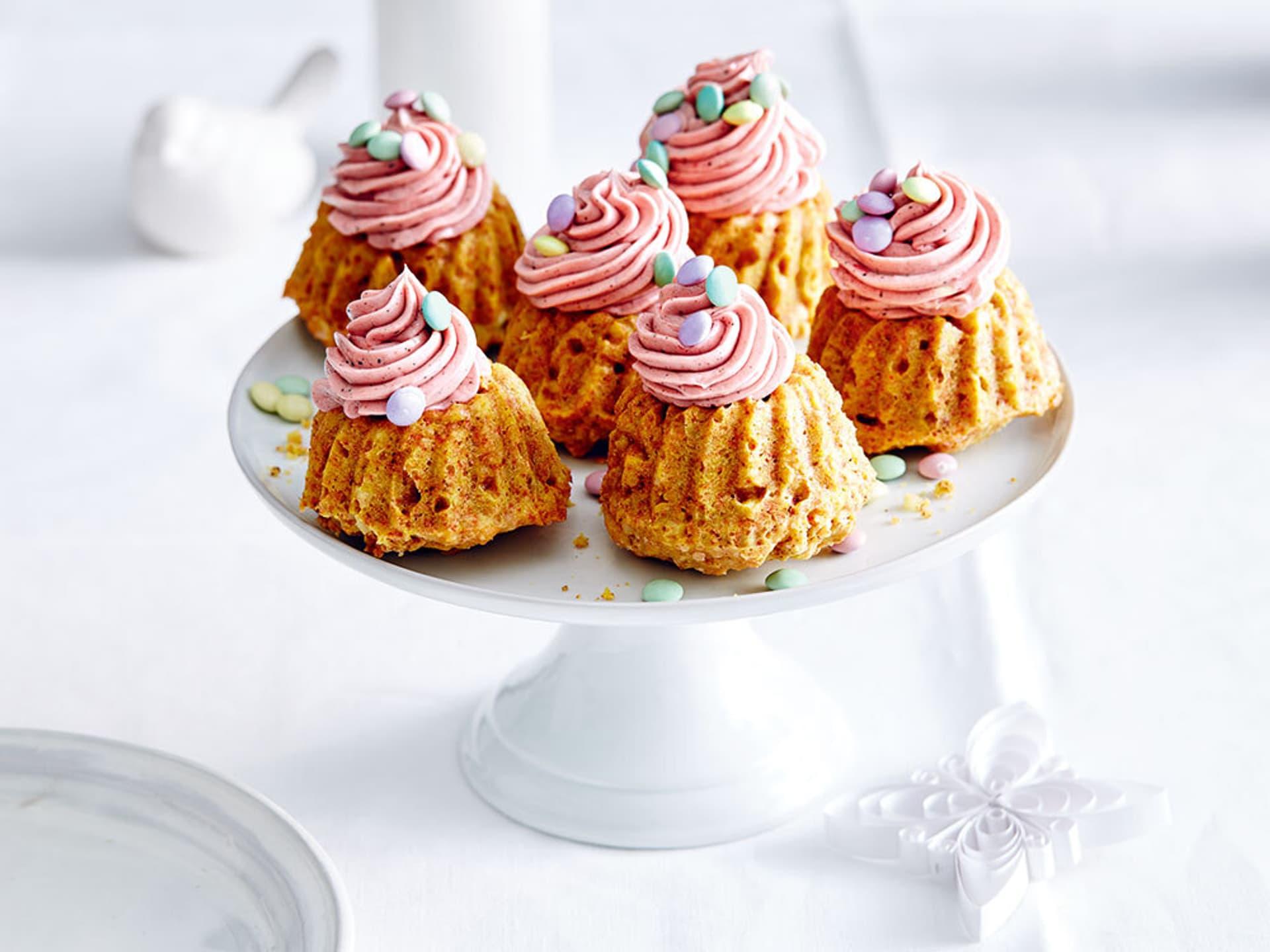 Auf einer weißen Porzellanetagere liegen sechs kleine Küchlein, verziert mit Rosa Frosting und winzigen Schokolinsen in Pastellfarben