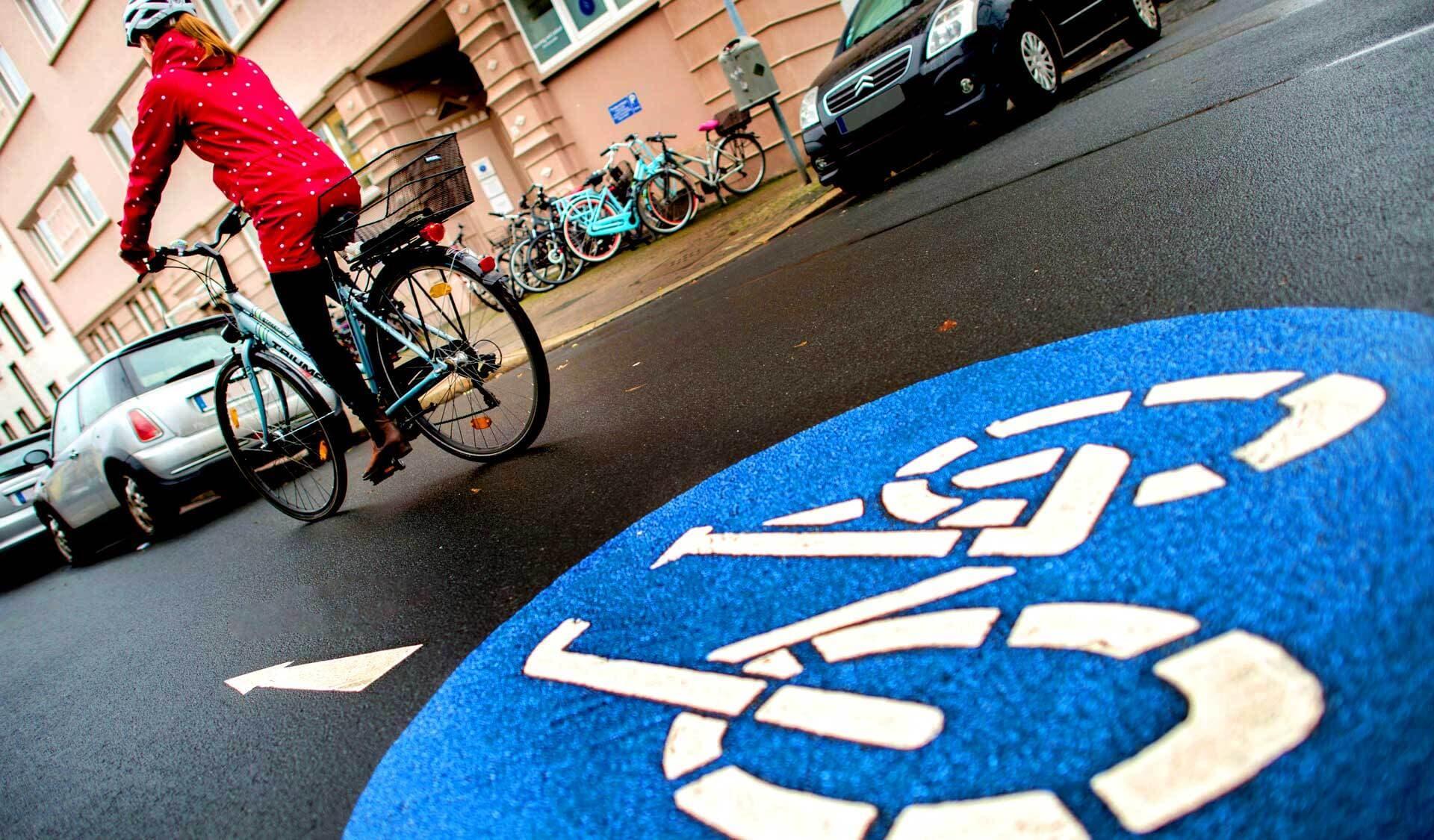 Eine Radfahrerin fährt auf der Fahrradstraße. Das blaue Fahrradstraßenzeichen ist auf dem Asphalt zu sehen