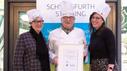 Drei Personen mit Kochmützen und einer Urkunde