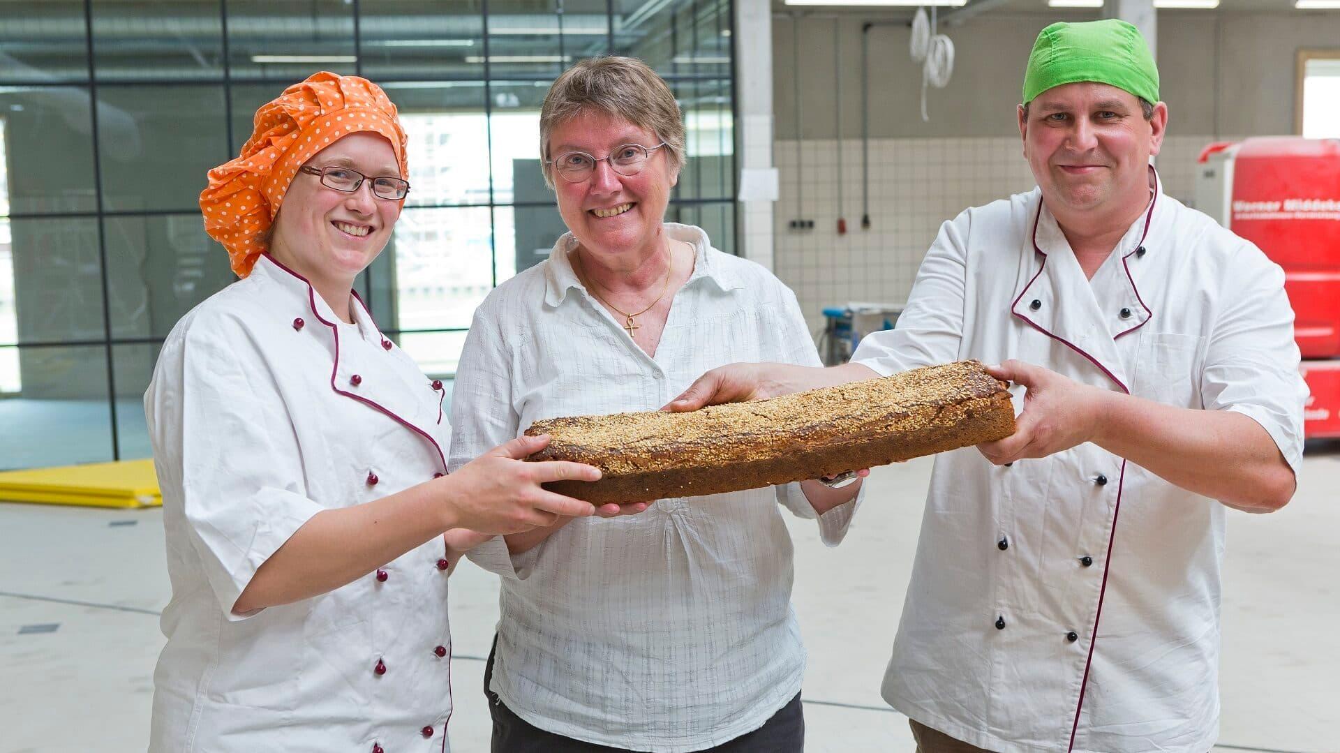 Bäckerin Franziska Glandorf, Cibaria-Gründerin Rike Kappler und Bäckermeister Stefan Lewe halten das erste Brot in Händen, das in der neuen produktionsstätte gebacken wurde.
