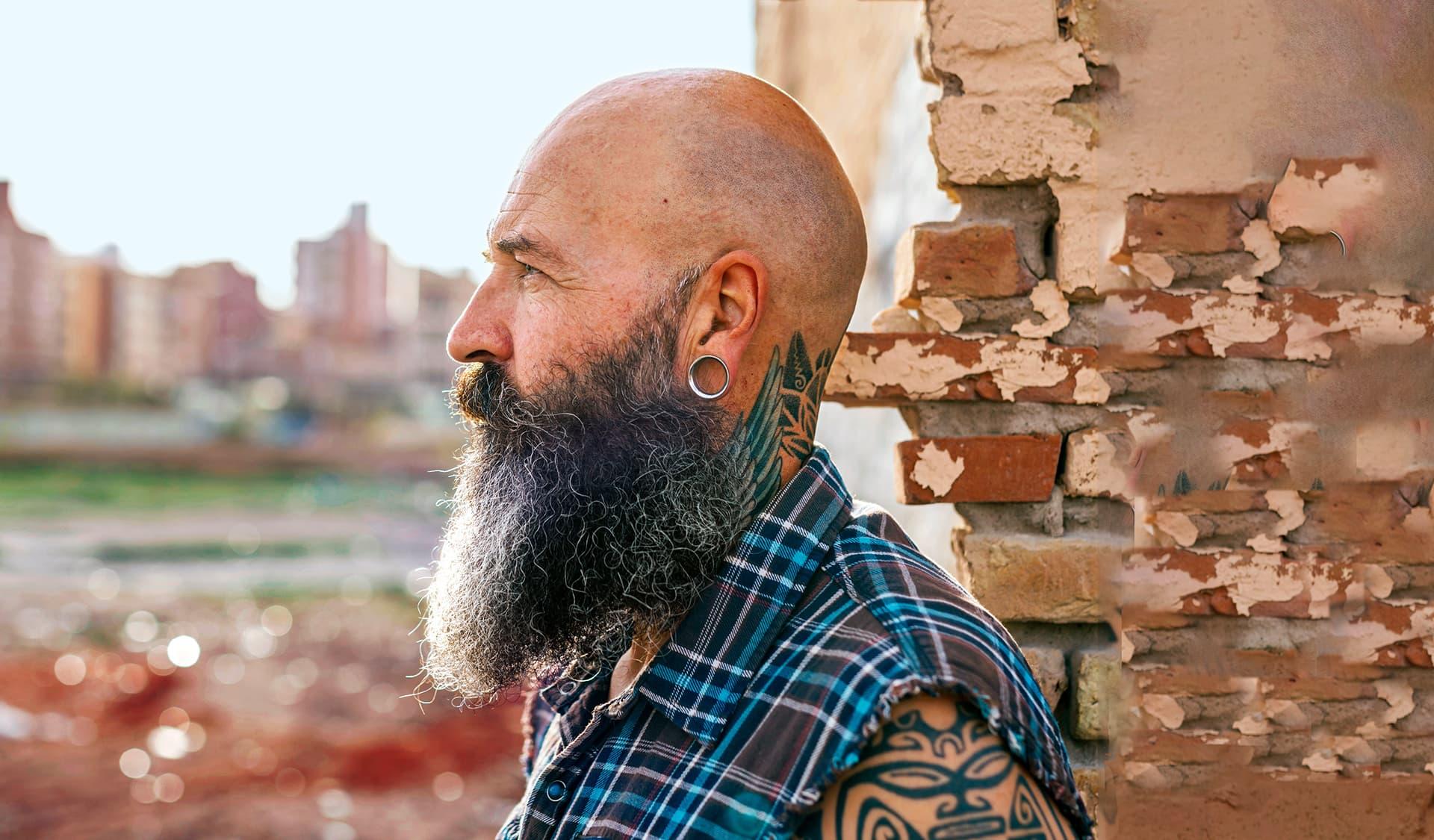 Mann mit grau-meliertem Rauschebart im Profil.
