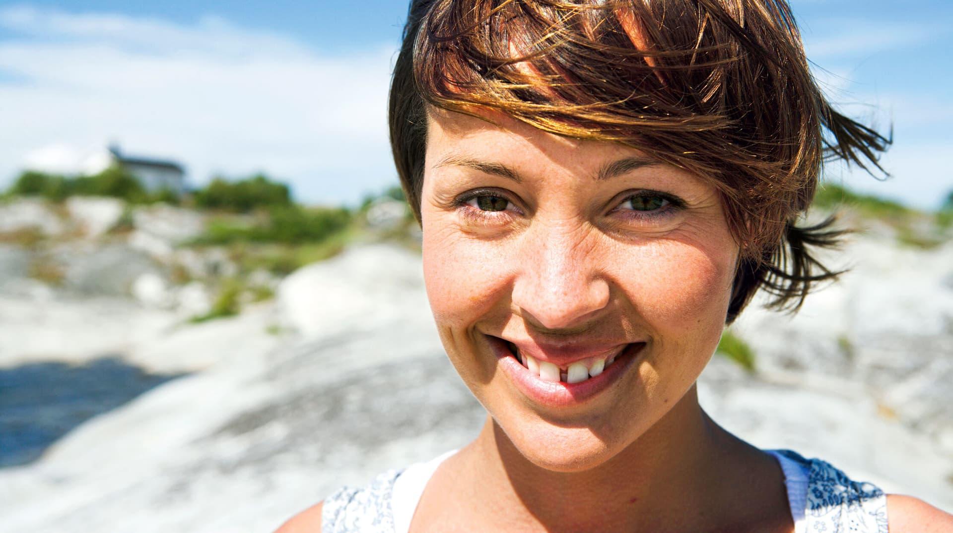 Lächelnde Frau mit Zahnlücke in der Sonne, im Hintergrund Dünen, ein Haus und ein wenig vom Meer.