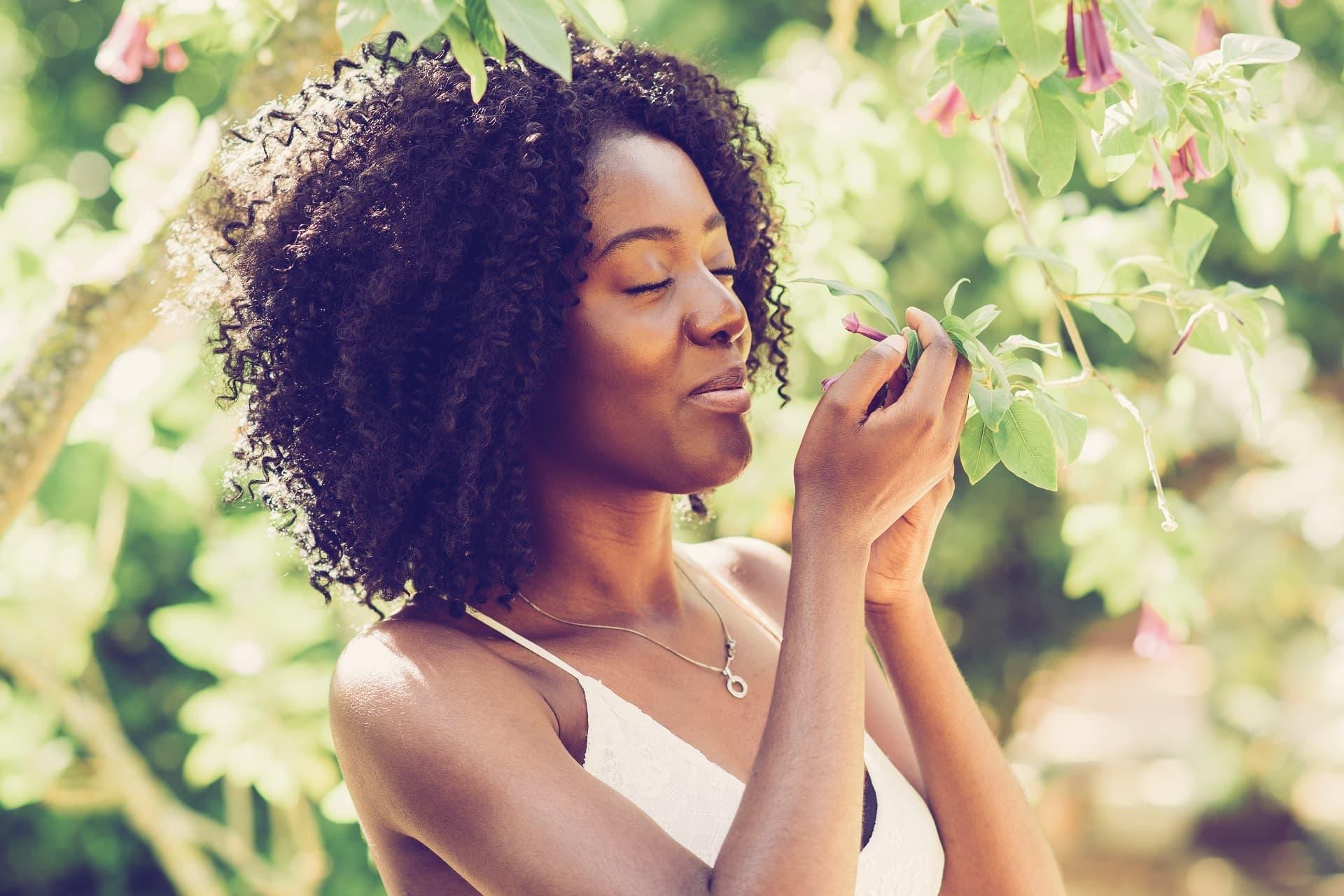 Frau riecht an Blüte