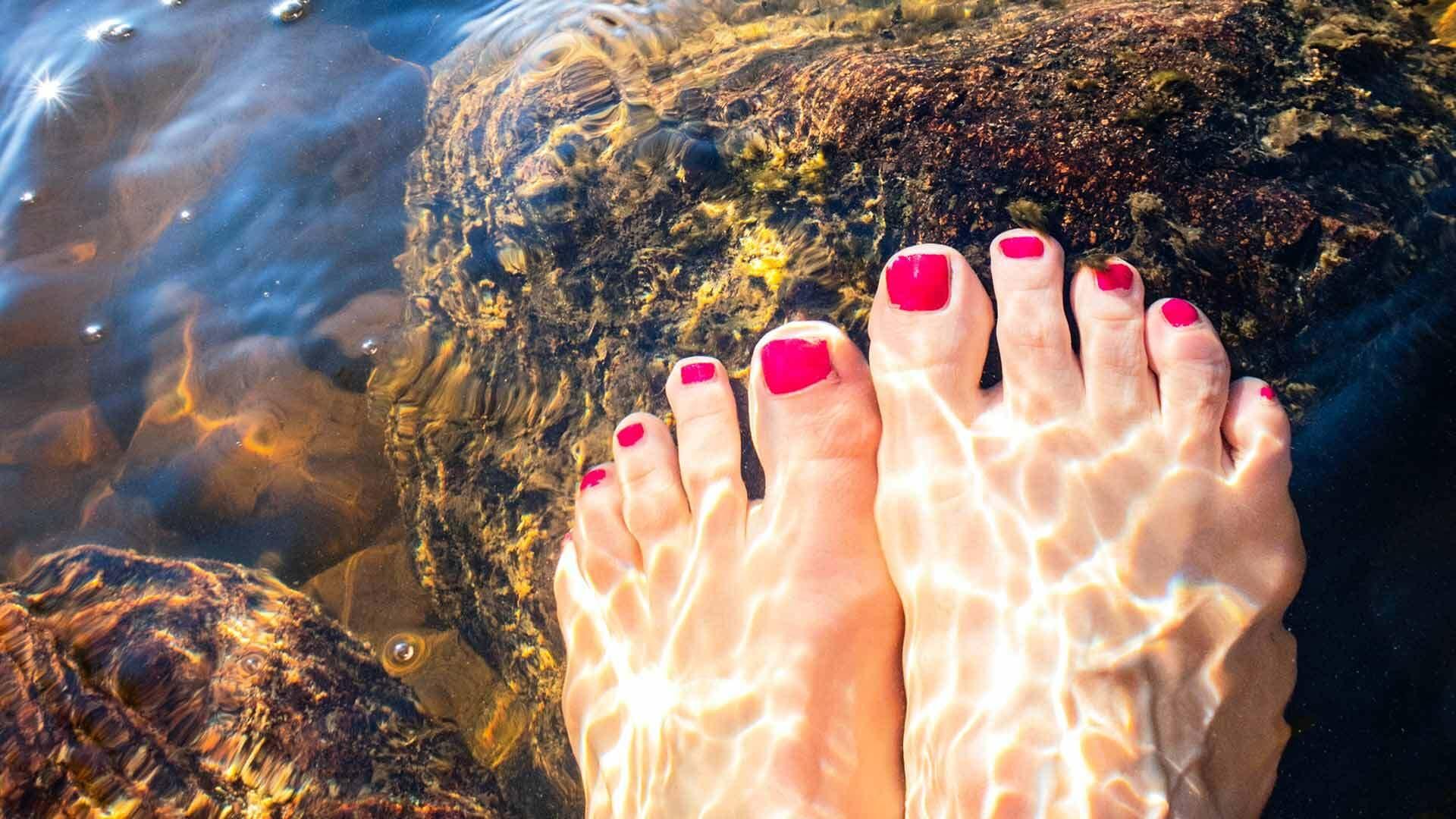 Mit Nagellack lackierte Zehen im Meerwasser