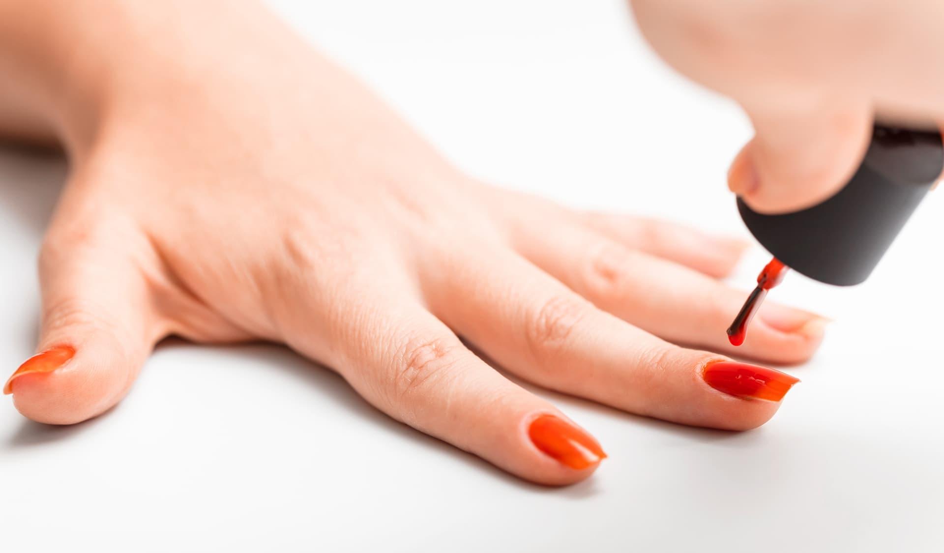 Eine Hand mit rot lackierten Nägeln.