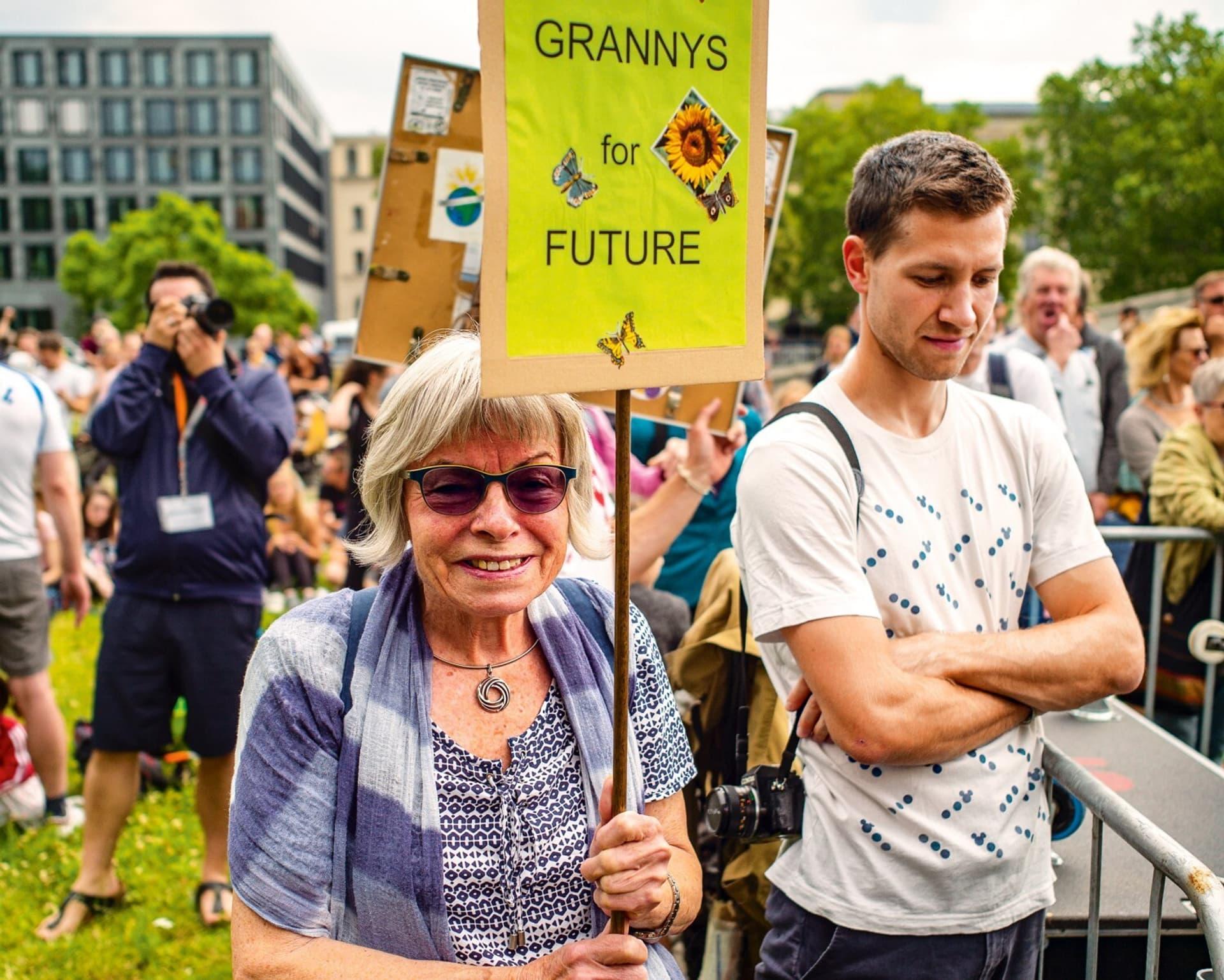Auf dem Bild ist eine Frau mit grauen Haaren und lila Schal zu sehen, die ein Demoschild mit der Aufschrift Grannys for Future hoch hält.