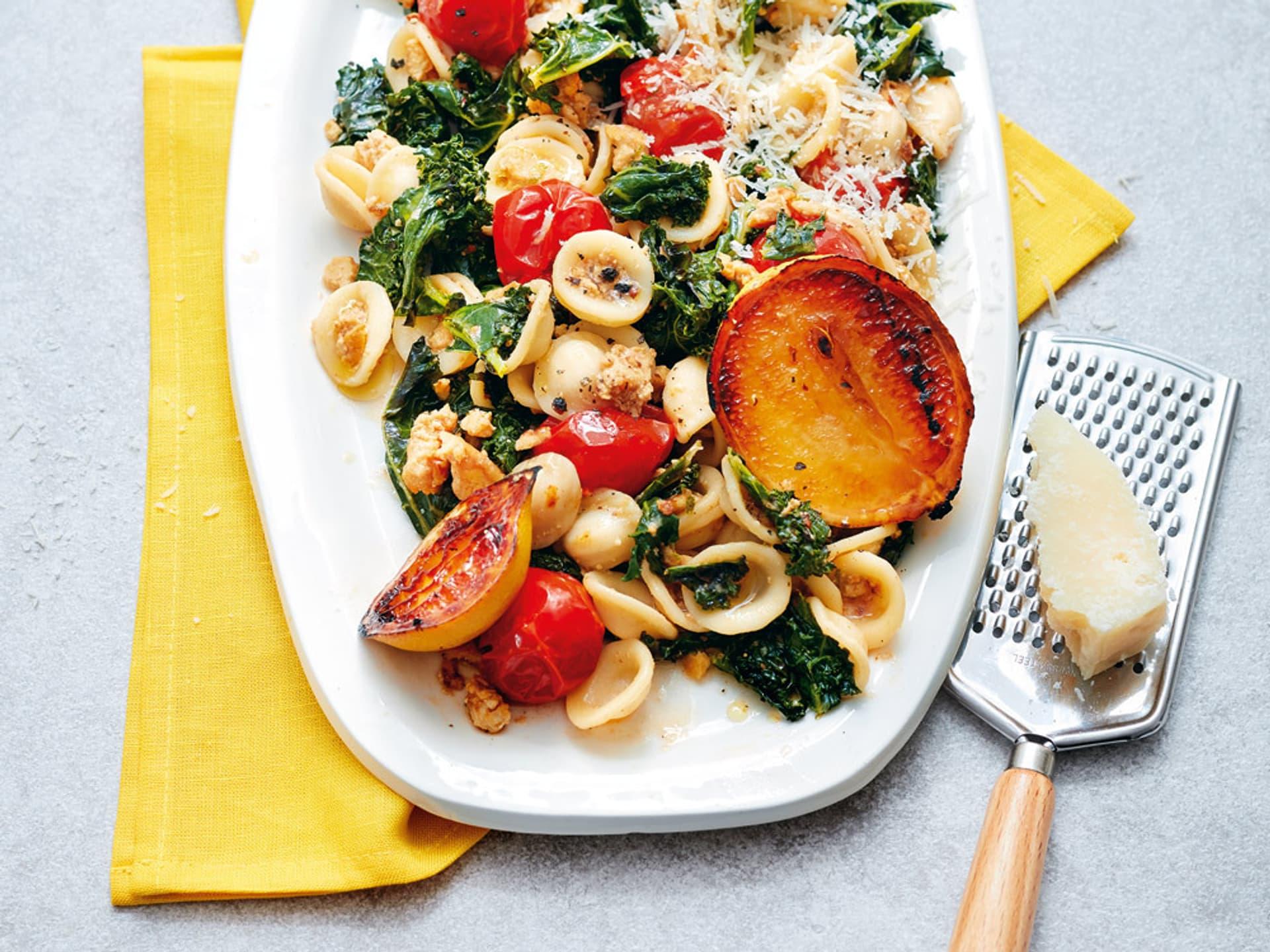kleine Teigkringe angerichtet mit Spinat, Tomaten und geröstetem Apfelsinen auf einem weißen Teller