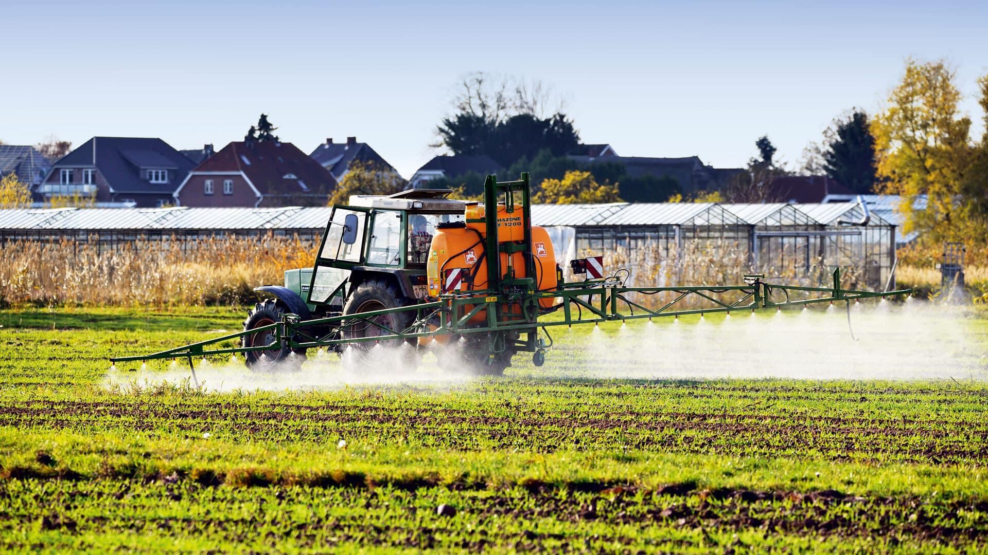 Traktor sprüht Pestizide auf ein Feld