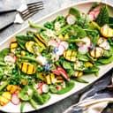 ovale Salatplatte mit Bohnen, Pflücksalat, gegrillten Kartoffeln und Radieschenscheiben
