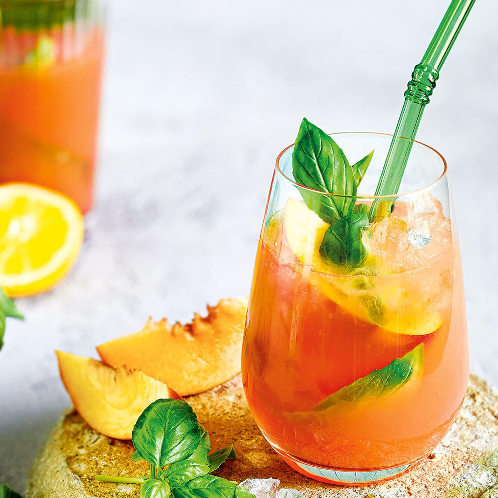 Glas mit orangenfarbenem Cocktail, garniert mit Basilikum, mit grünem Trinkhalm