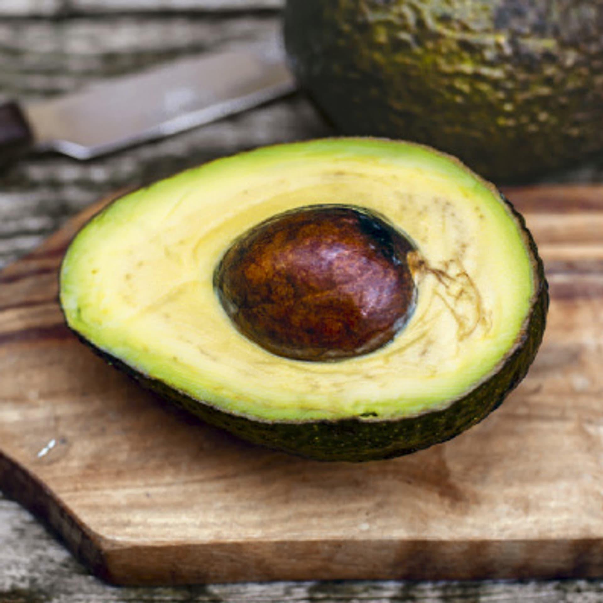 Eine offengeschnittene Avocado liegt auf einem Schneidebrett, daneben ein Messer.