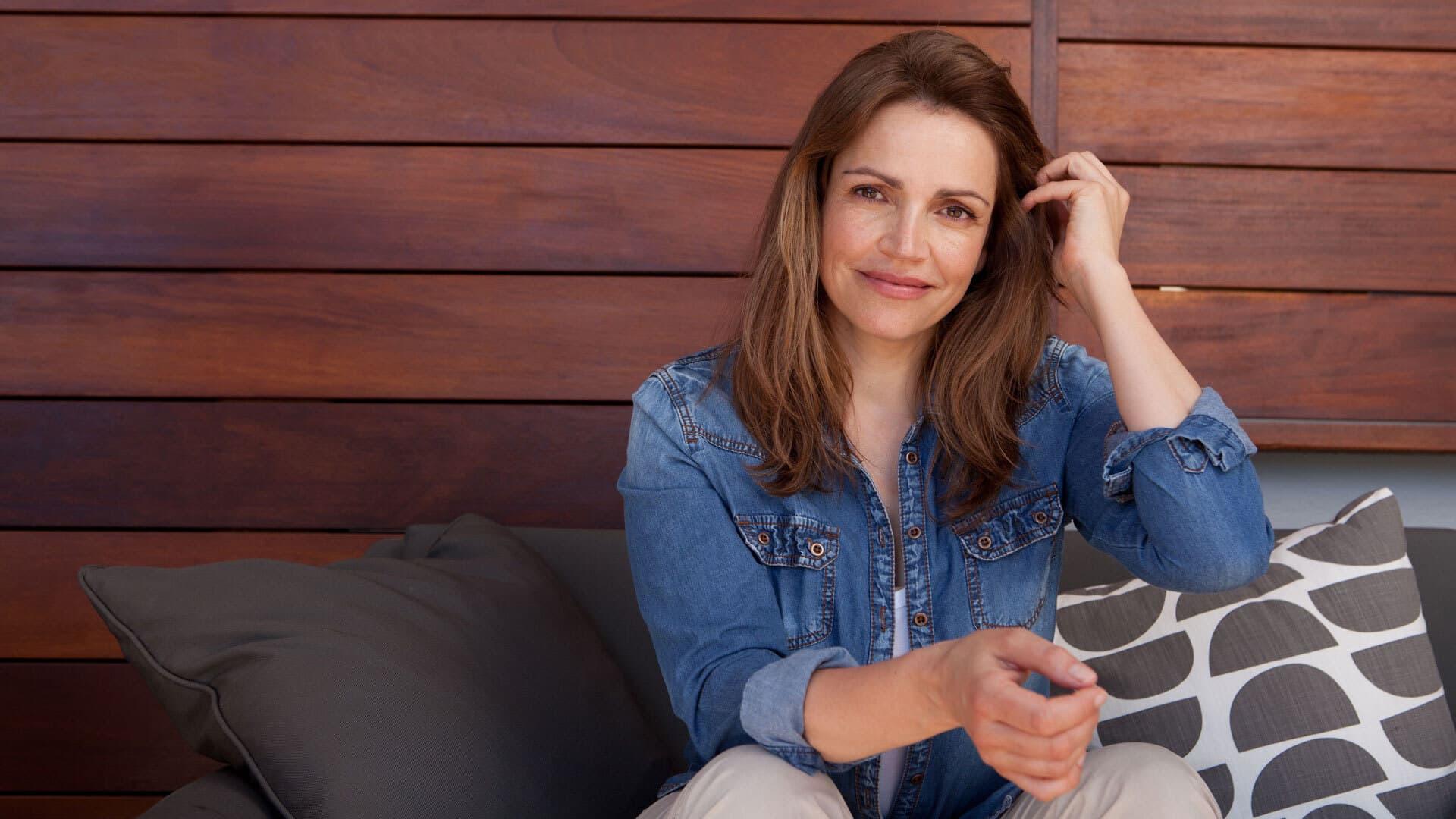 Rebecca Immanuel sitzt im Jeans-Hemd auf einer Terrasse