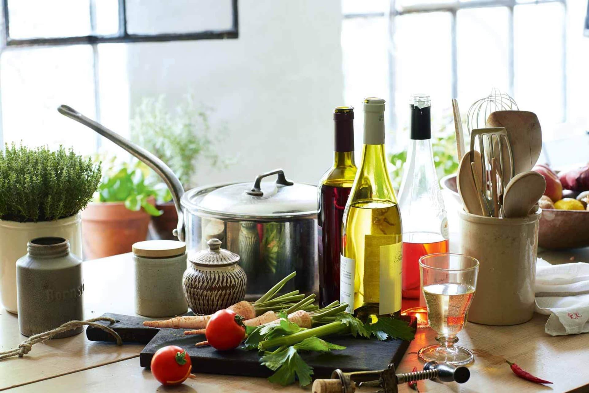 Verschiedene Weine stehen in Flaschen neben Töpfen und Gemüse in der Küche