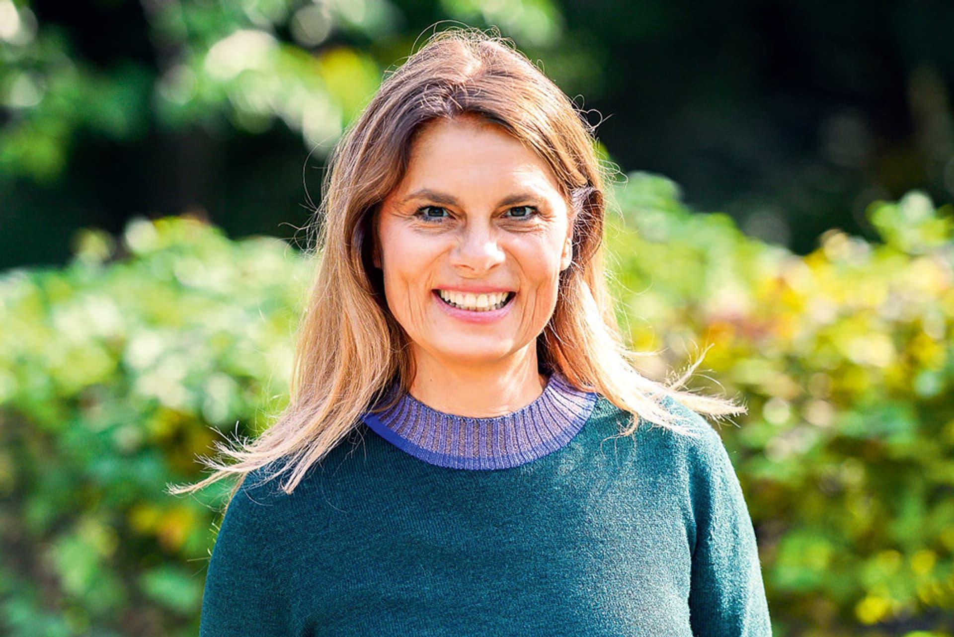 Sarah Wiener (helle Haut, langes hellbraunes, glattes Haar, grüner Wollpulli) steht im Grünen und lacht in die Kamera