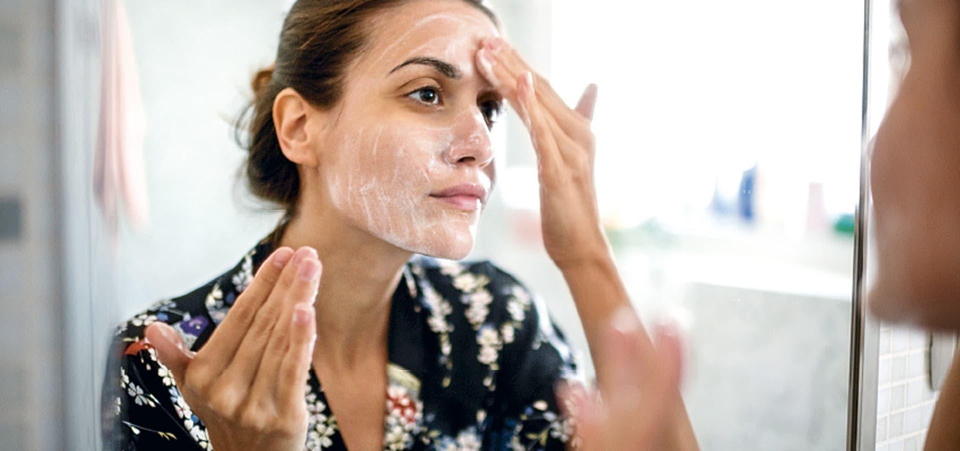 Eine Frau steht vor dem Spiegel und cremt sich das Gesicht ein.