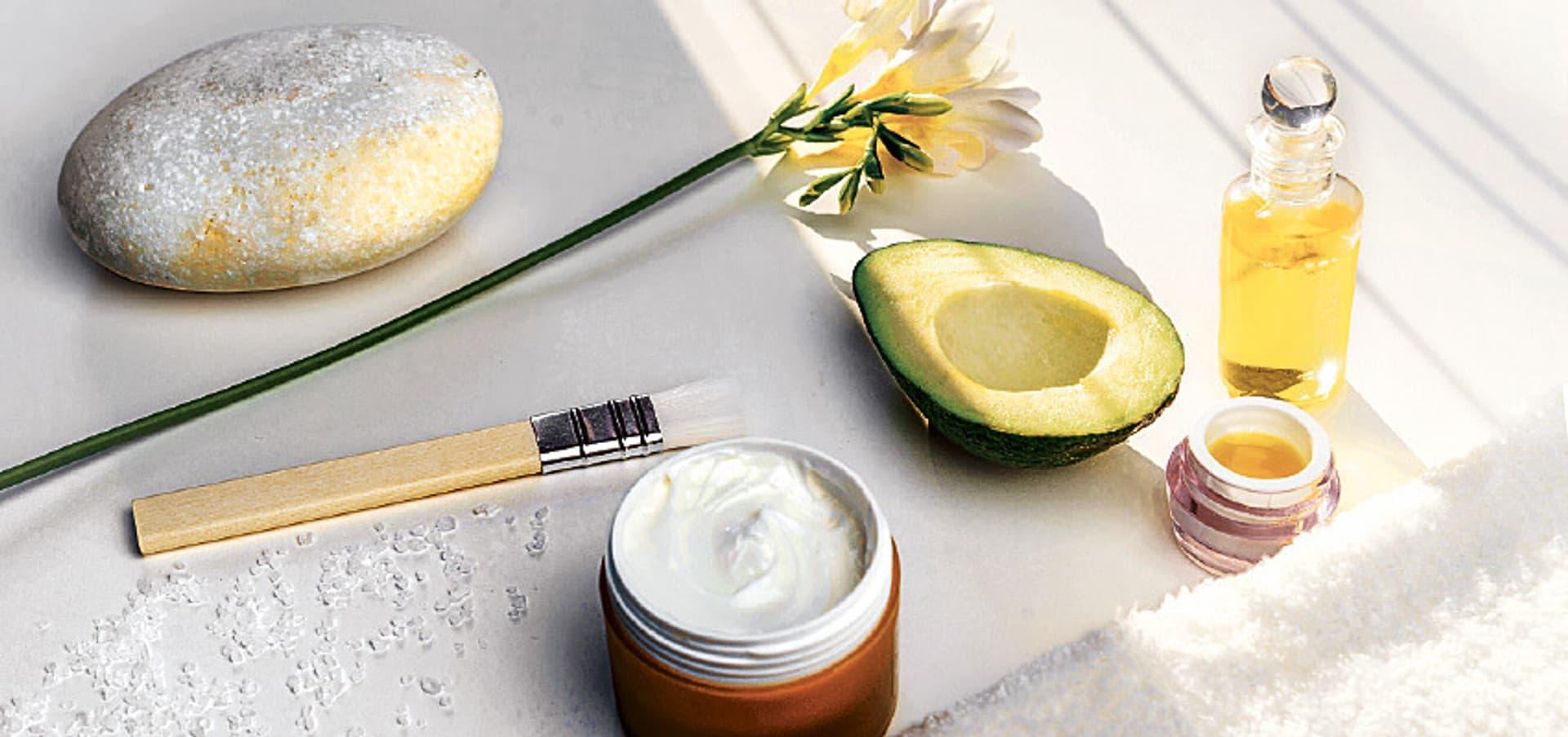 Stimmungsvolles Kosmetikbild mit einer Avocadohälfte, einer Cremedose und einem Pinsel.