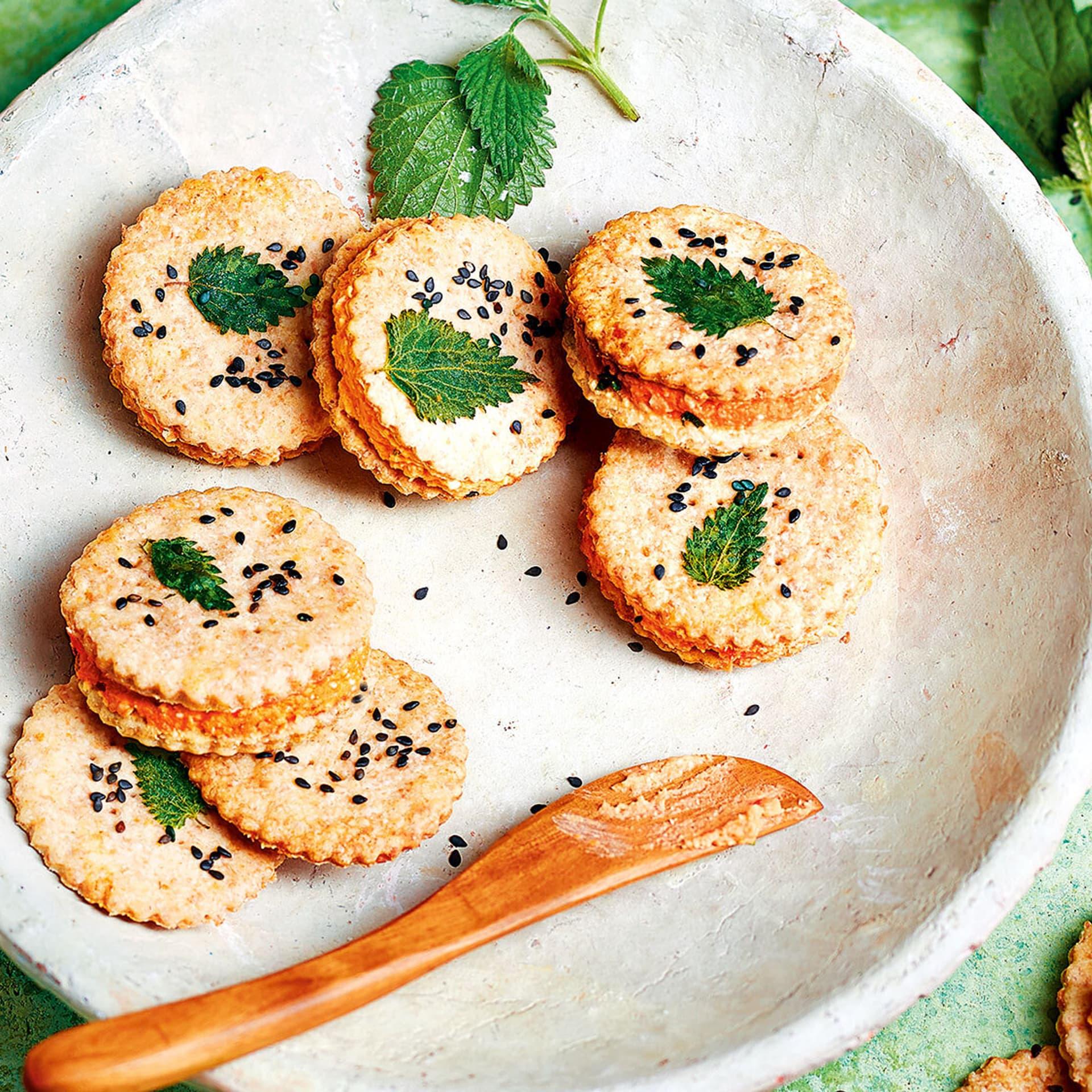 Doppeldecker-Cracker mit schwarzem Sesam und Brennnesselblättchen bestreut auf einem Teller