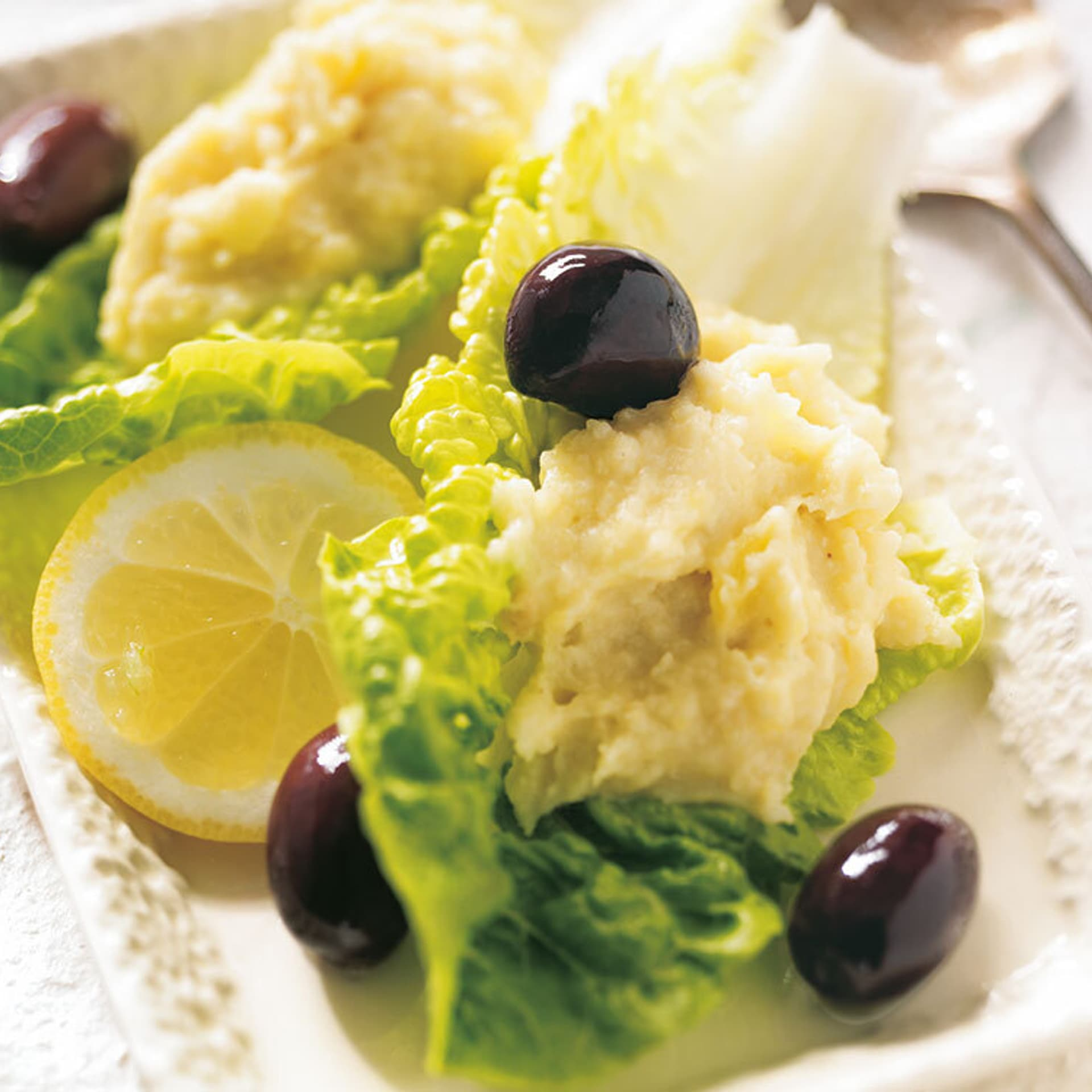 Ein gelber Aufstrich garniert mit schwarzen Oliven und Salatblättern