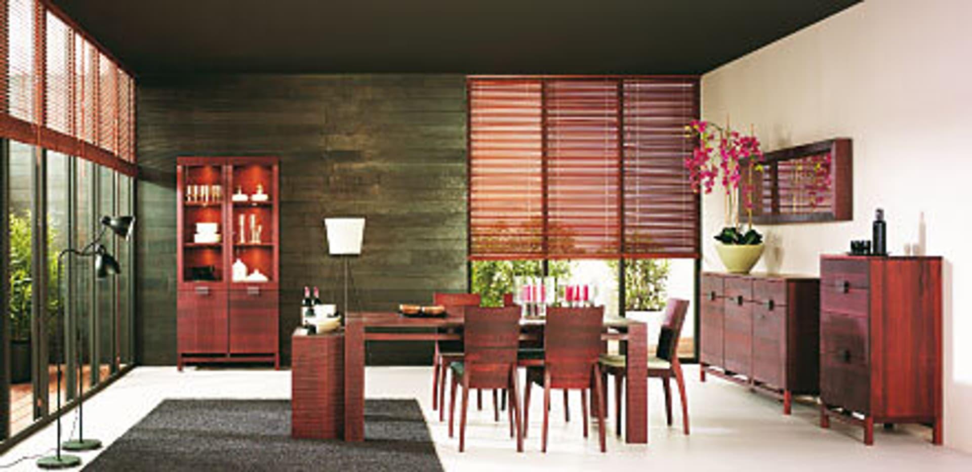 Ein eleganter Raum voller Möbel in rötlichem Holz