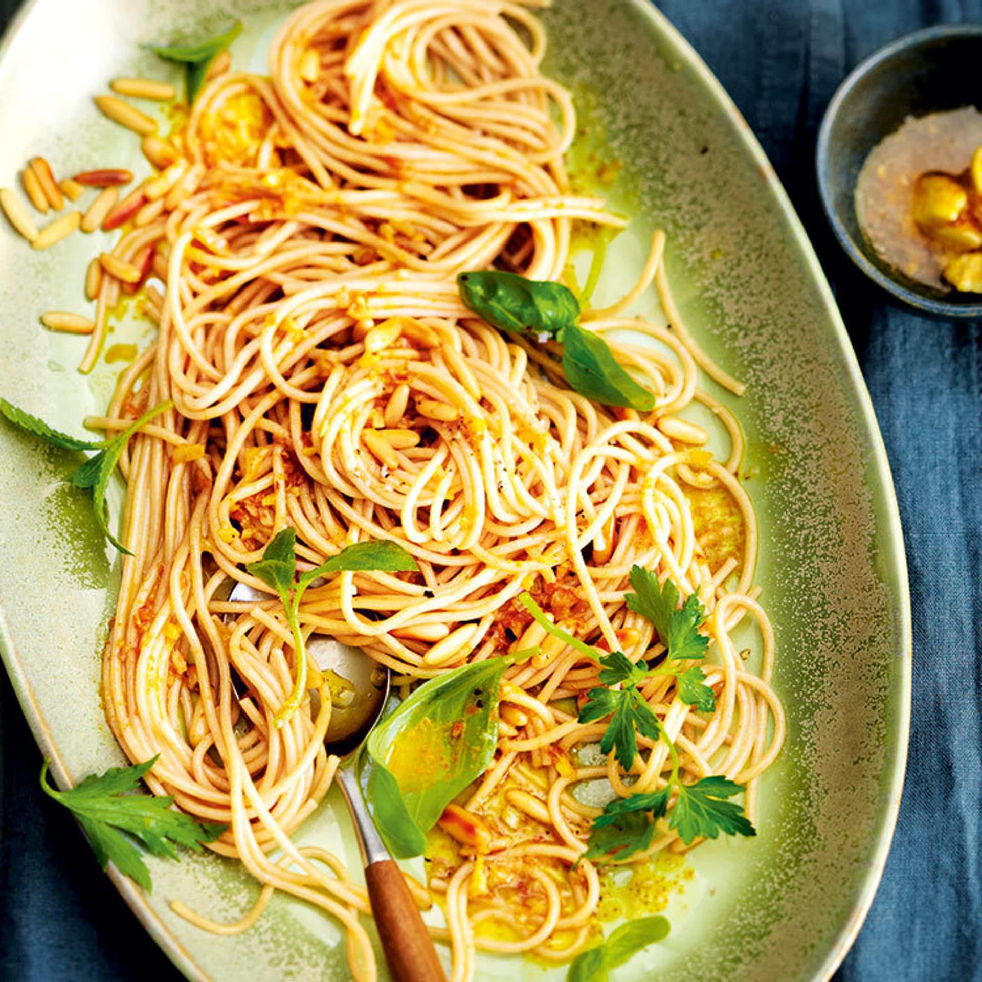 Ein ovaler Teller von oben gefüllt mit Spaghetti, Käutern und Gewürzen.