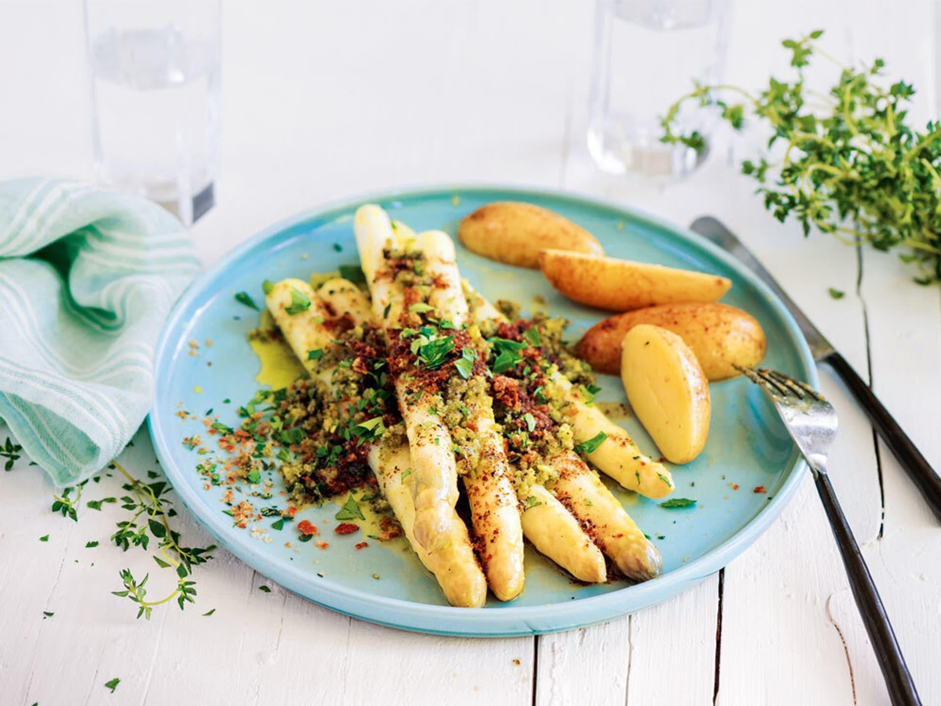 Spargel mit Kräuterkruste und Kartoffeln auf einem hellblauen Teller