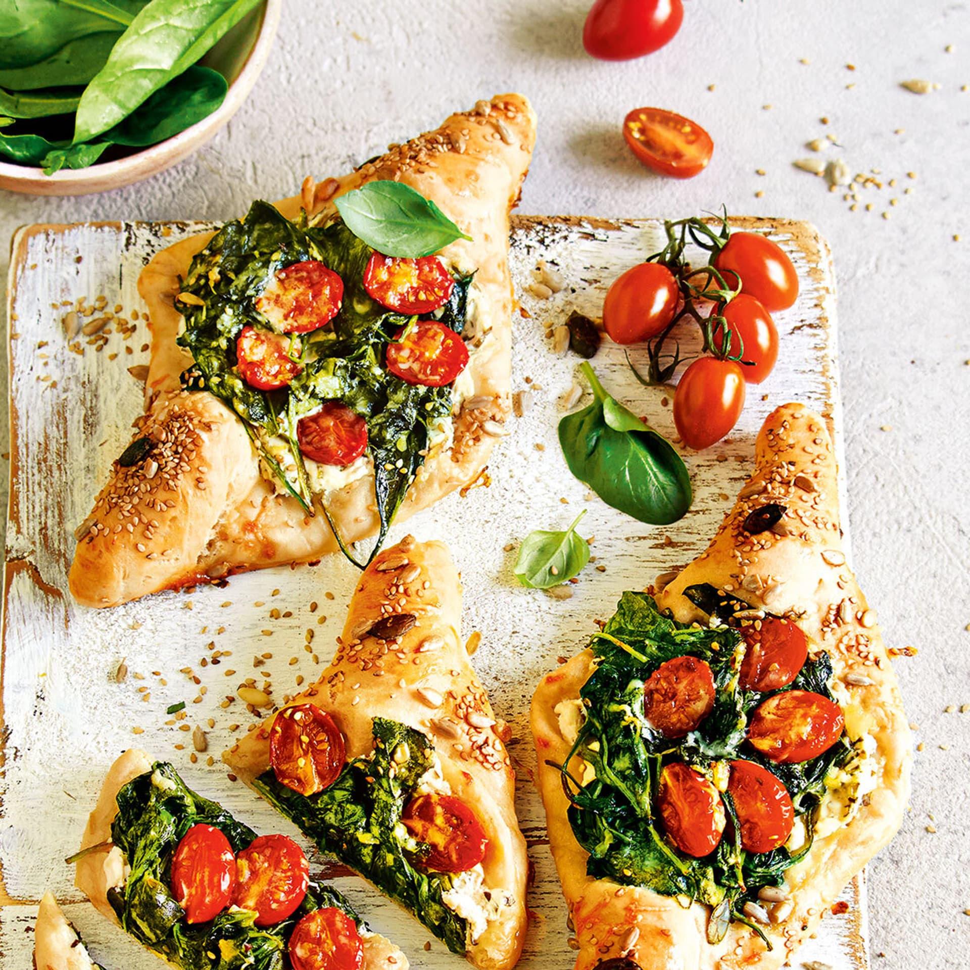Rautenförmige, kleine Pizzas belegt mit Kirschtomaten udn Spinat