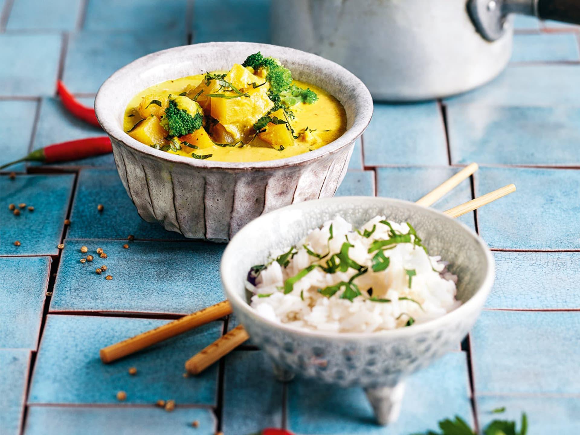 Zwei weiße kleine Schüsseln. Eine voller weißem Reis, eine voller gelbem stückigem Curry.