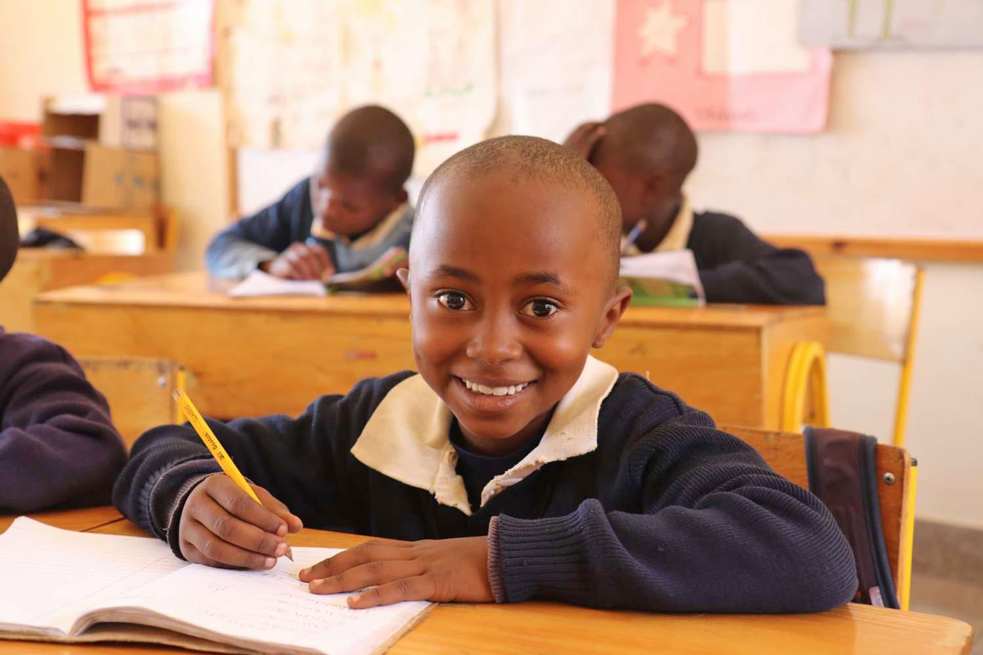 Ein Kind sitzt an einer Schulbank und lächelt in die Kamera