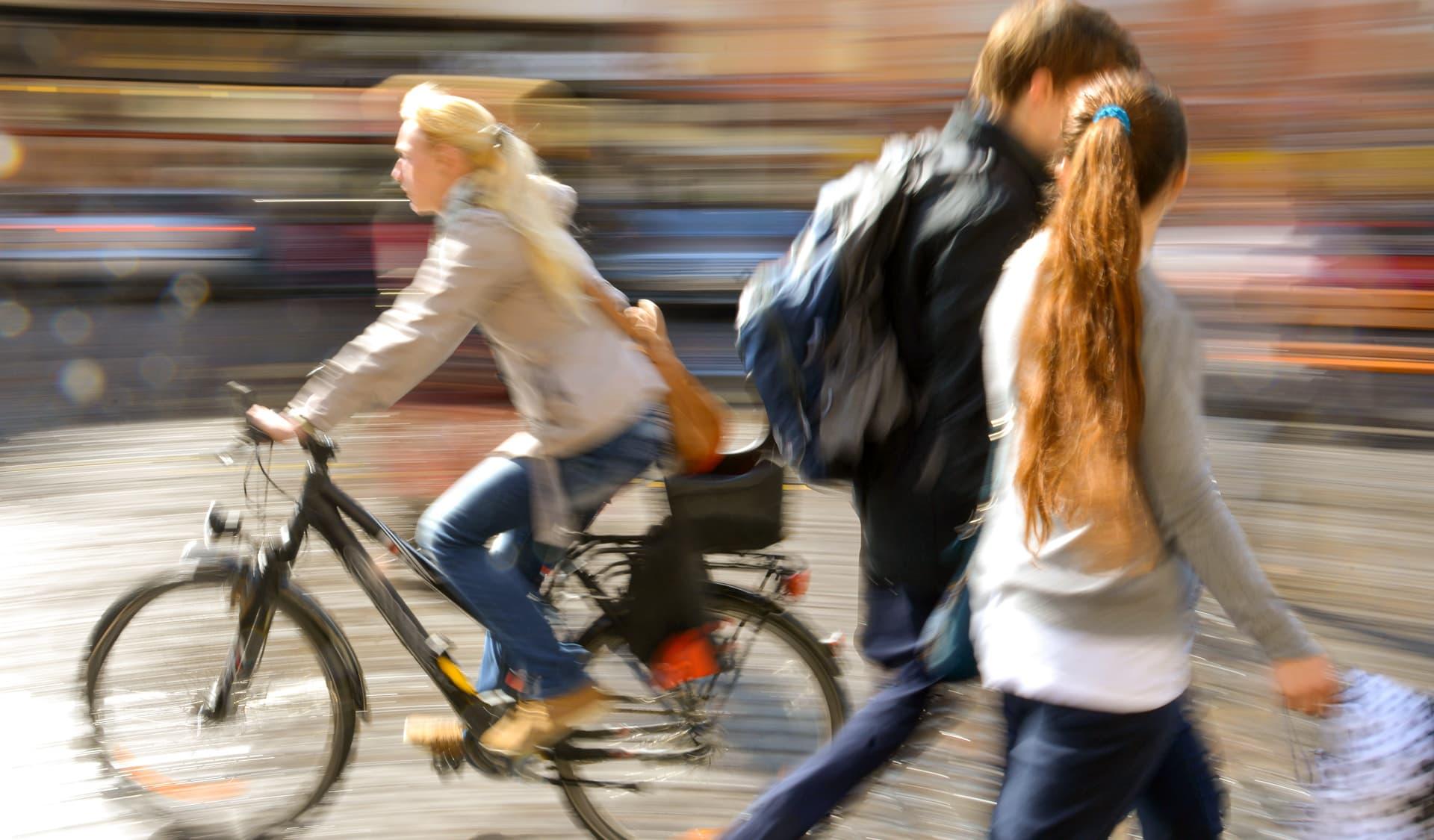 Eine Frau fährt auf dem Fahrrad an zwei Menschen vorbei