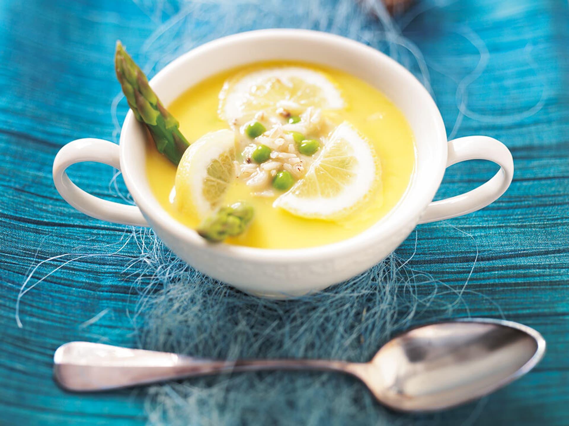 eine gelbe Suppe in einer weißen Suppenschüssel, darin Zitronenscheiben, grüner Spargel und Erbsen