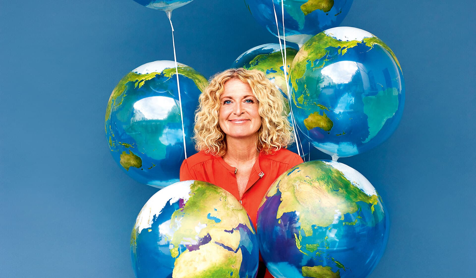 Susanne Fröhlich umgeben von Luftballons, die wie Erdkugeln aussehen