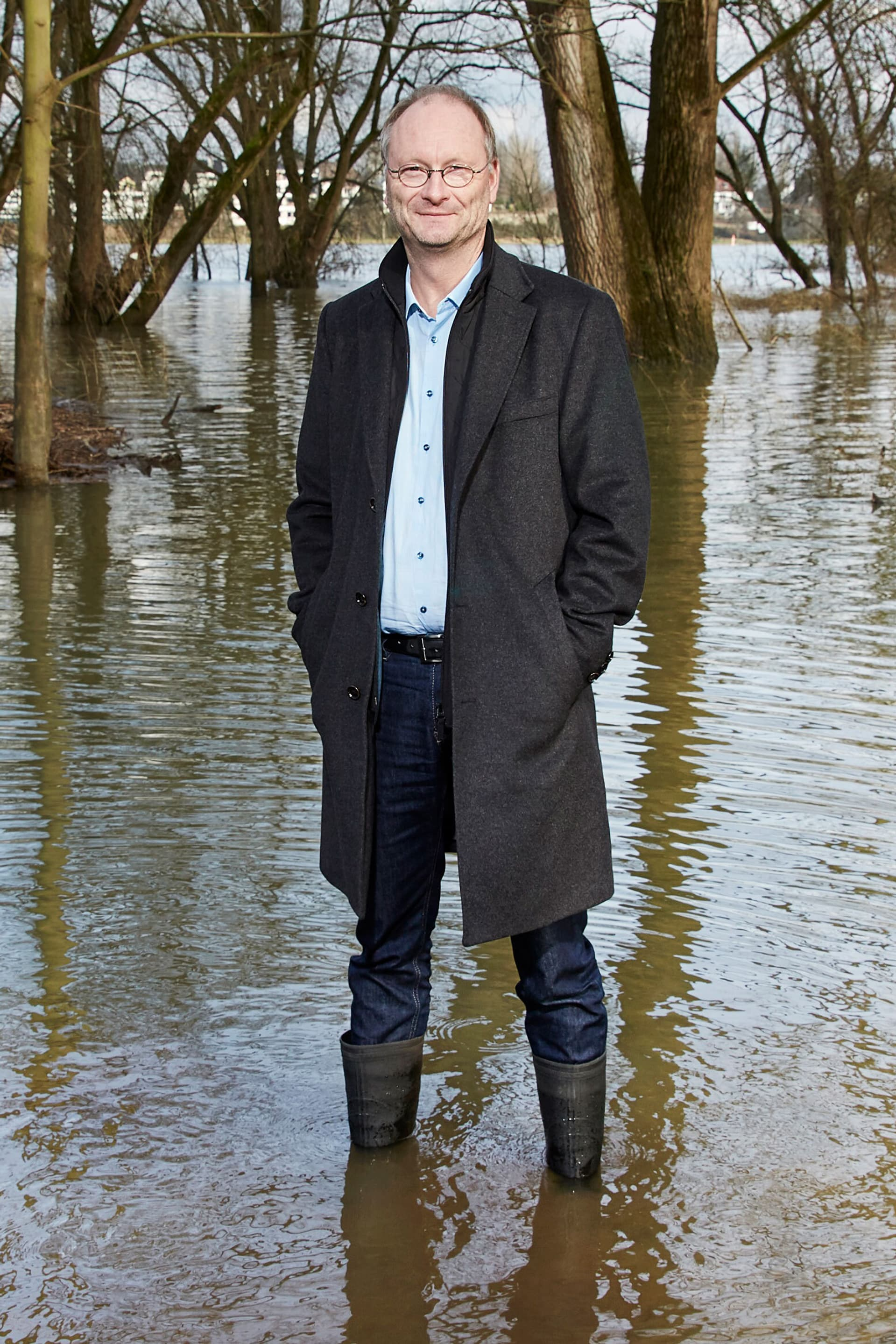 Sven Plöger steht mit Mantel und Stiefeln im Hochwasser vor Bäumen