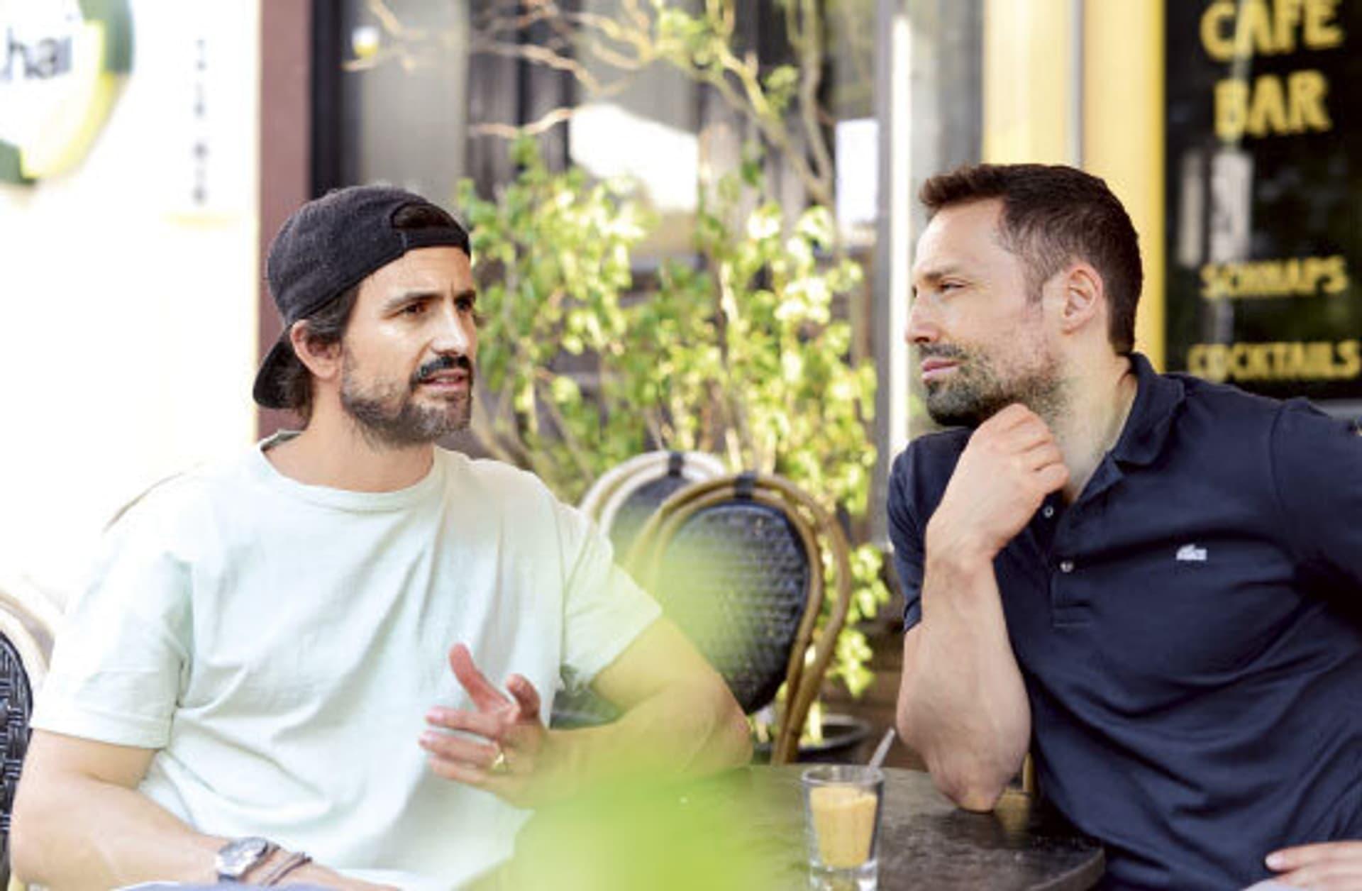 Schauspieler Tom Beck und Schrot & Korn Autor Renato Leo sitzen zusammen in einem Cafe und unterhalten sich.
