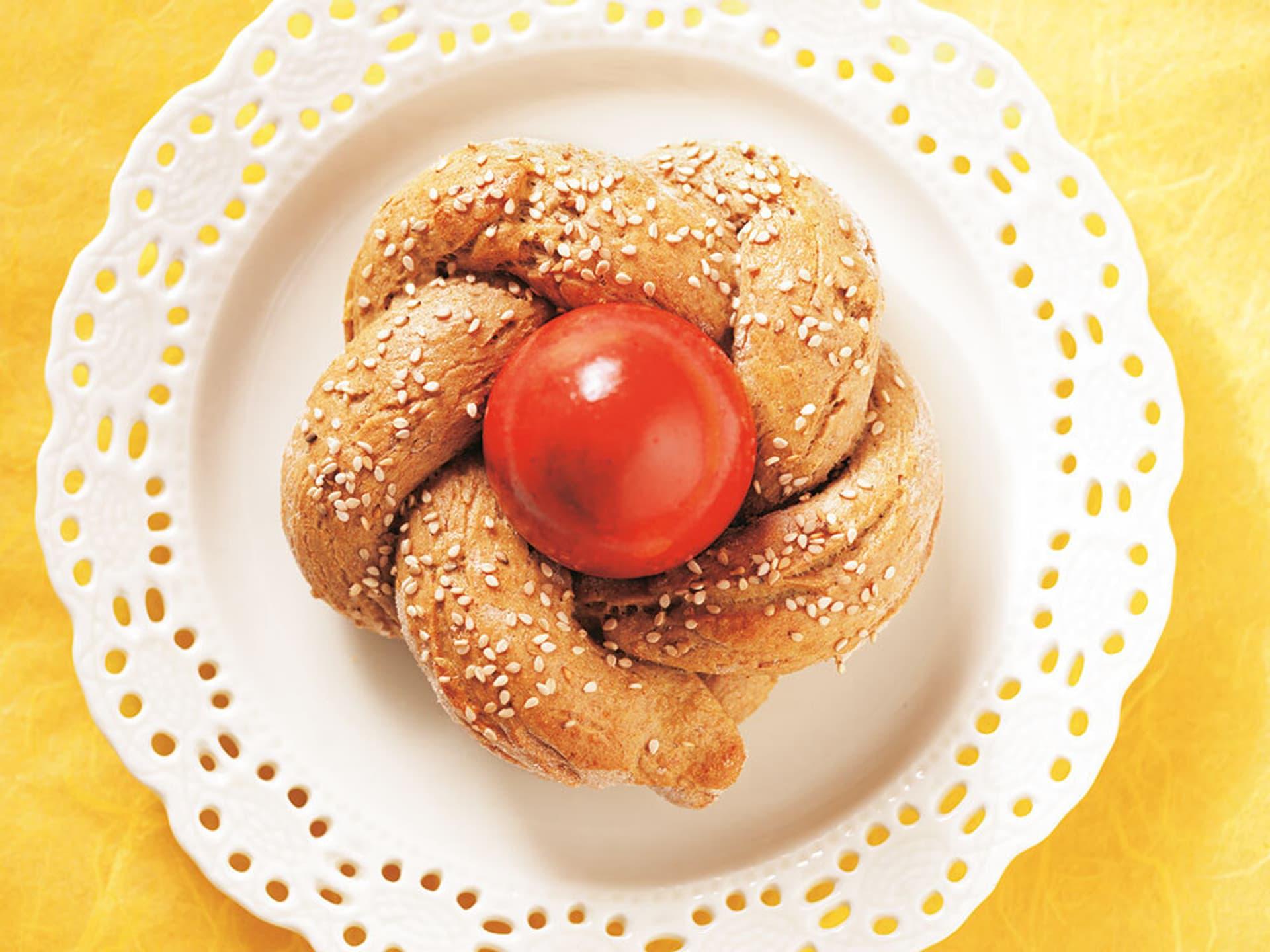 Ein Stück nestförmiges, mit Sesam bestreutes Hefegebäck, in dem ein rot gefärbtes Osterei sitzt