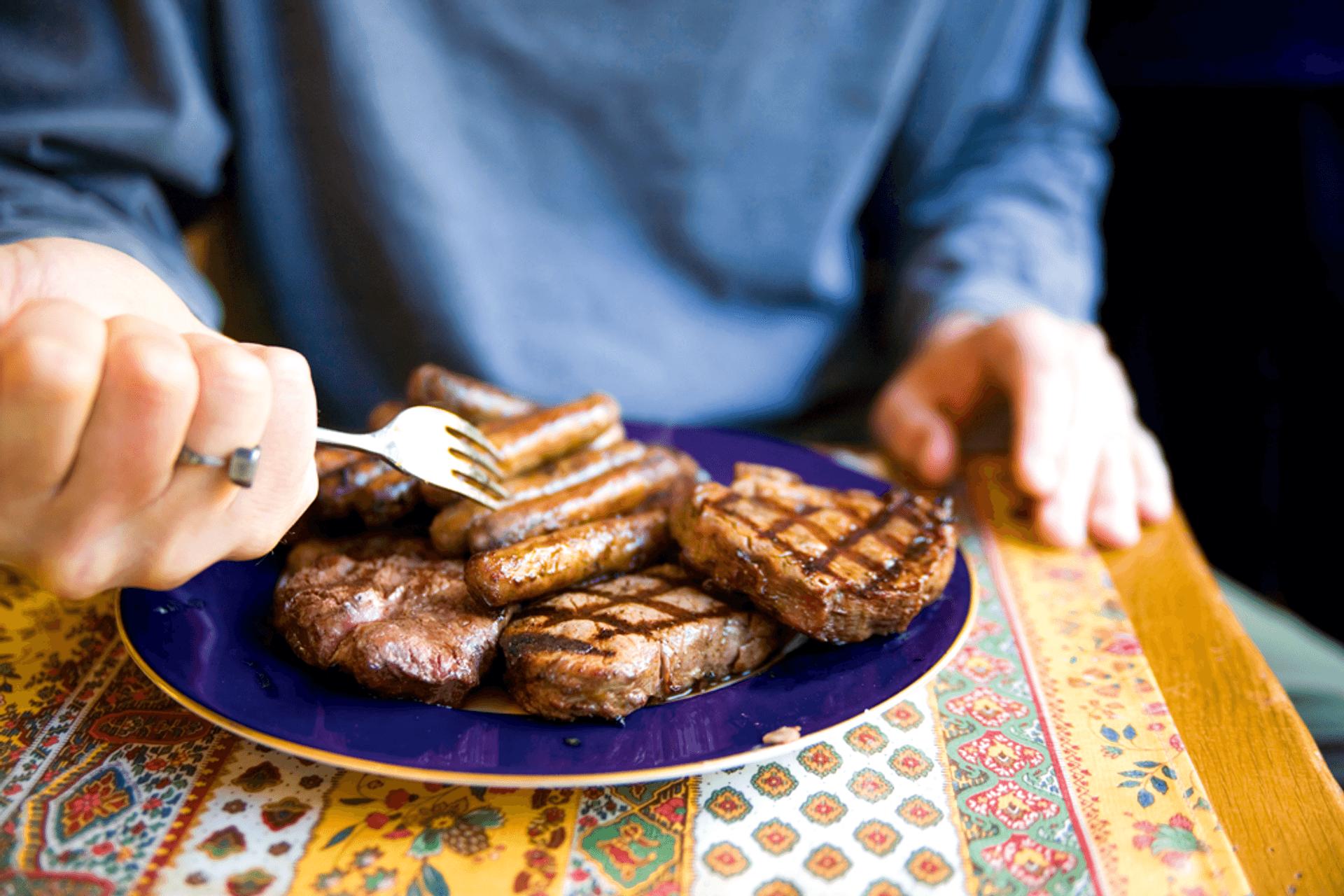 Ein blauer Teller voller Würstchen und Steaks