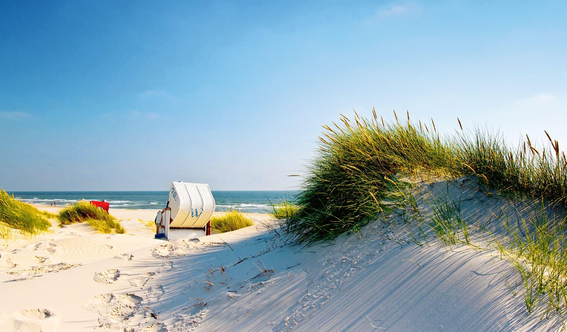 Blick vorbei an Sanddünen und Strandkörben auf das Meer.