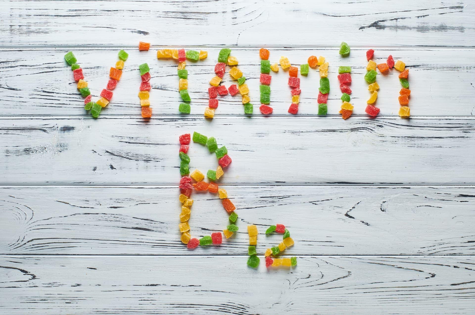 Vitamin B12 in bunter Schrift auf Holzboden