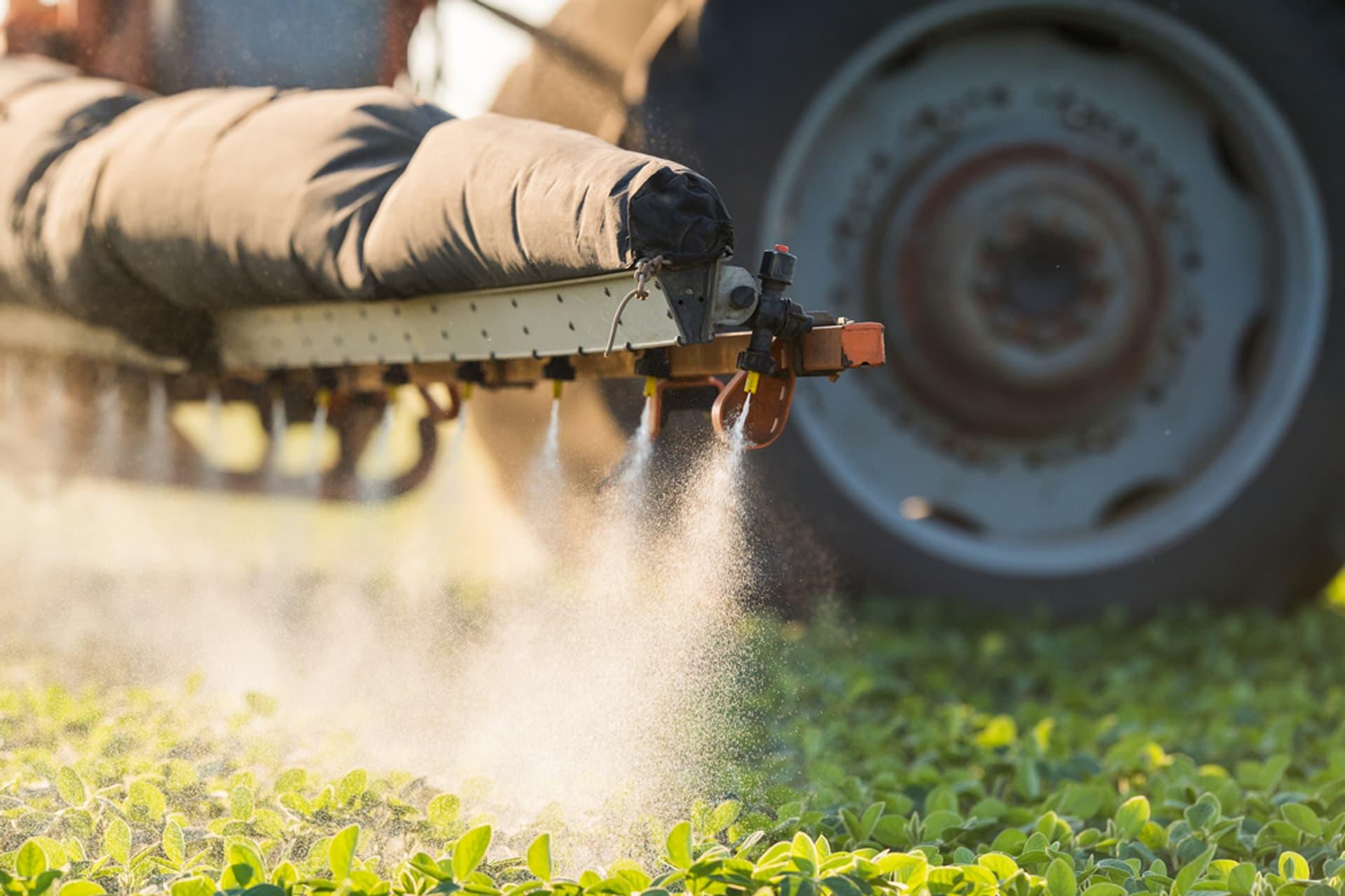 Ein Trecker sprüht Pestizide auf eine Wiese