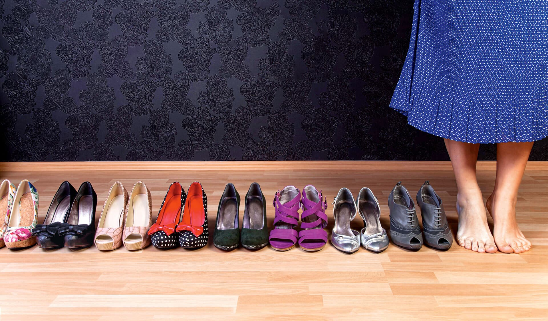 Ein paar nackte Frauenfüße und sehr viele Paar Schuhe in einer Reihe.